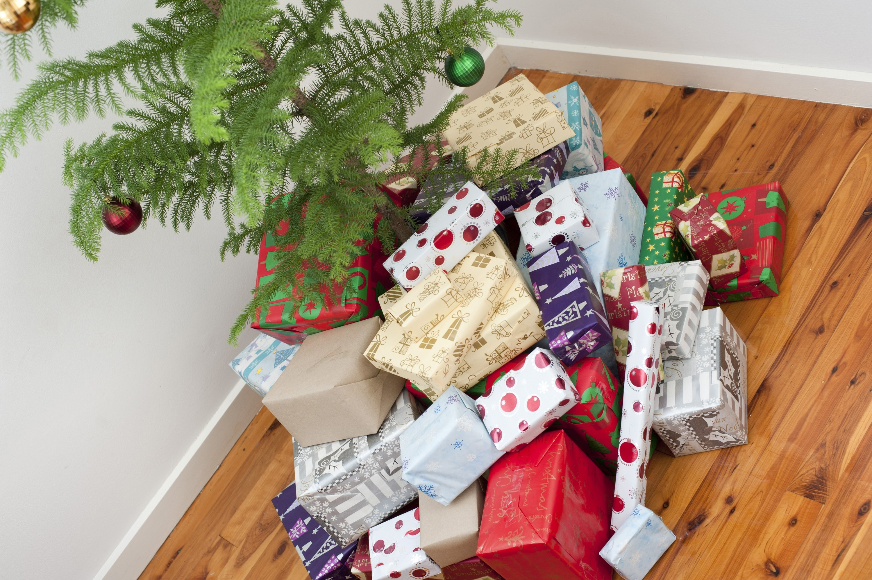 High angle view of a huge pile of colourful gift-wrapped Christmas gifts under the Christmas tree in all shapes and sizes for a joyful family celebration