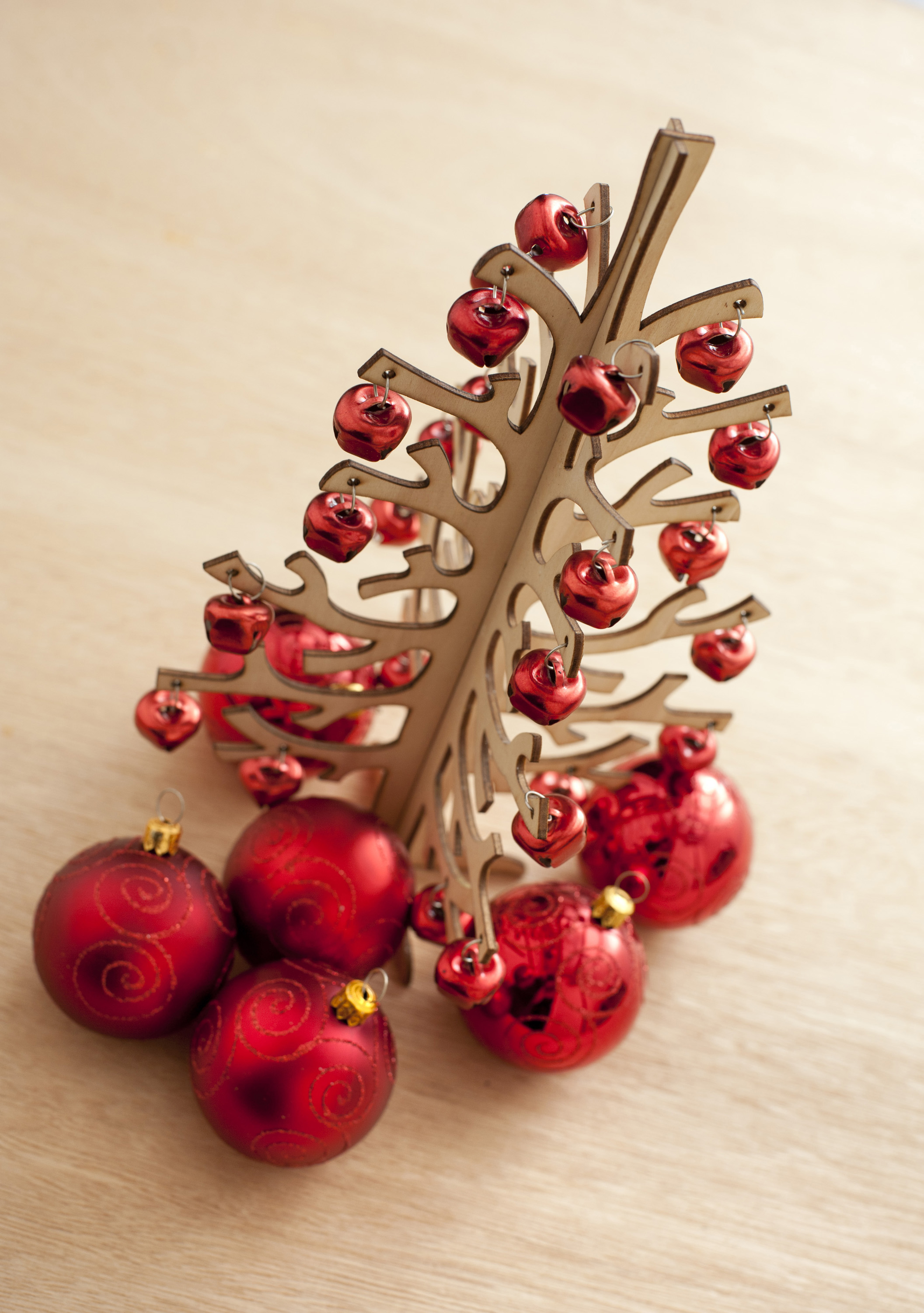 Close-up of wooden Christmas tree decorated with red balls.