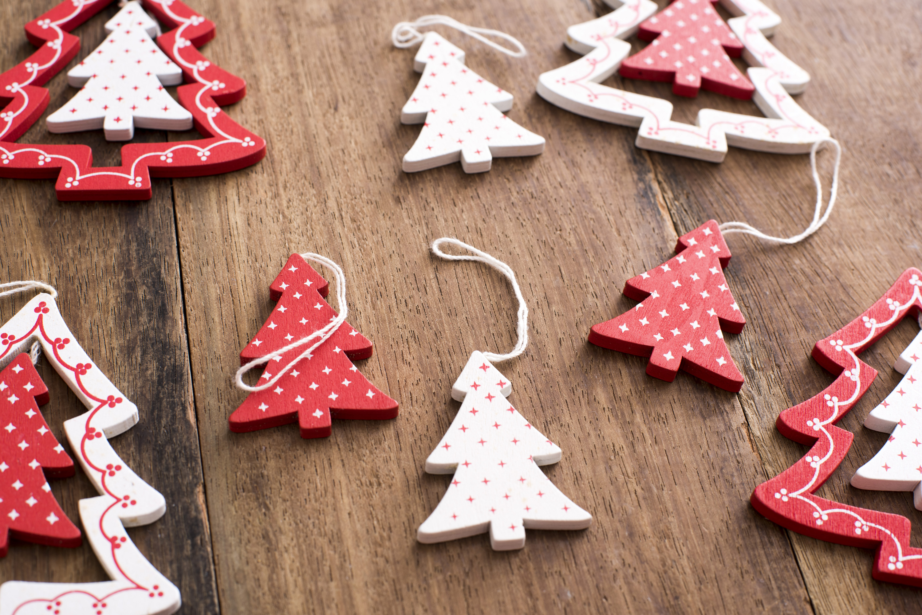 Wooden tree shaped Christmas ornaments with a decorative red and white pattern lying on a wooden table in a full frame view