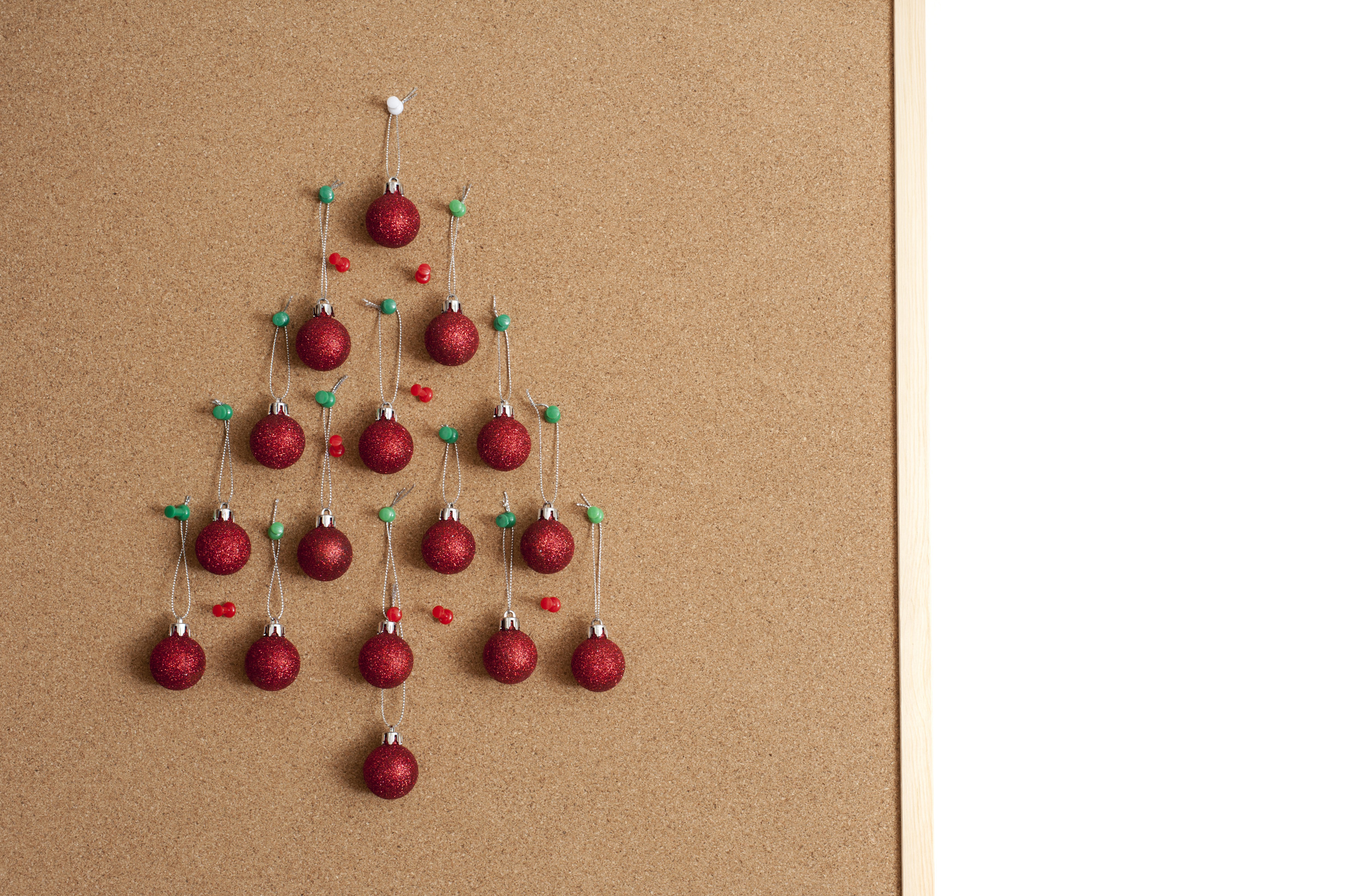 Office Christmas tree balls hanging on cork noticeboard board