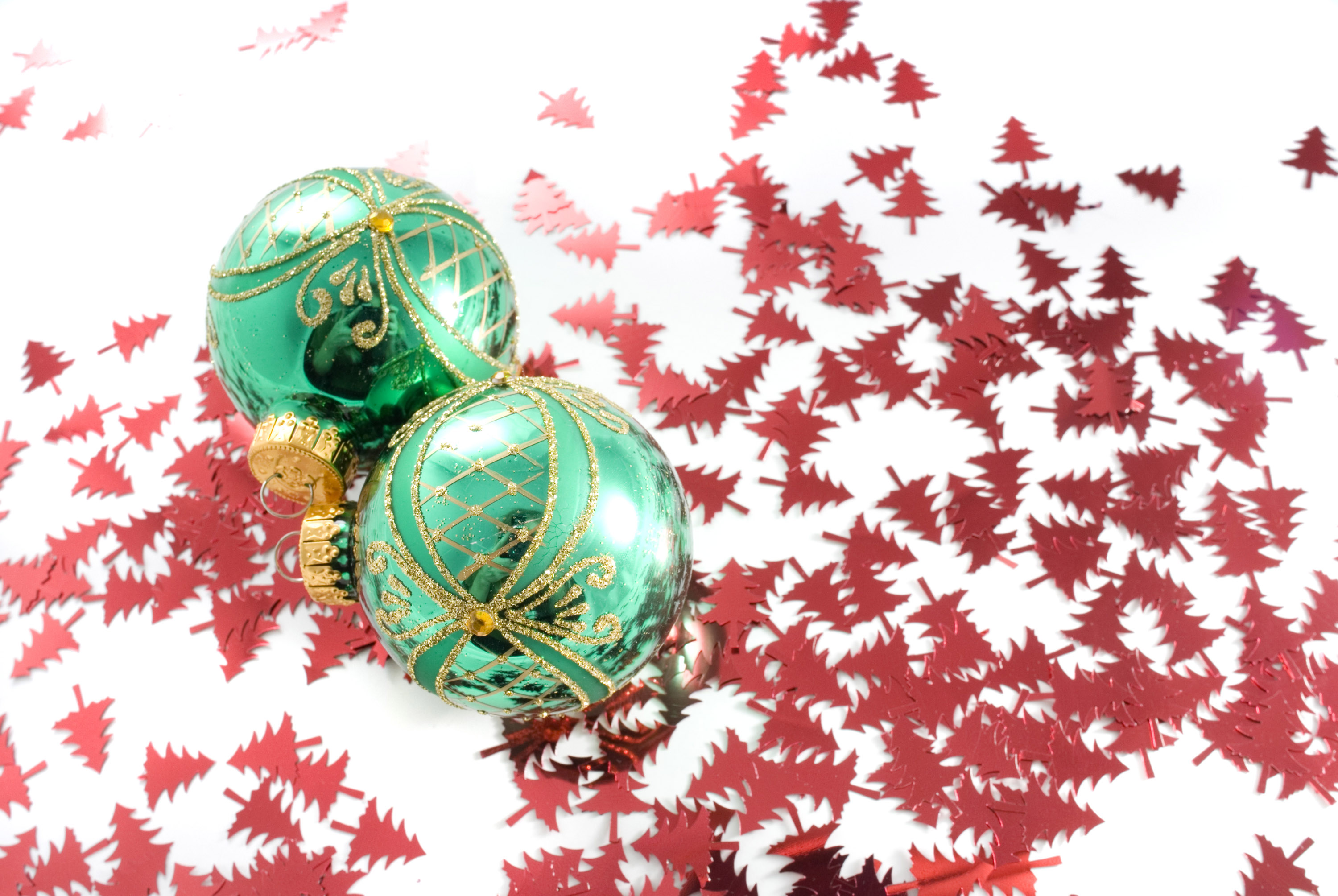 a festive background of red tree shaped confetti and two green reflective baubles