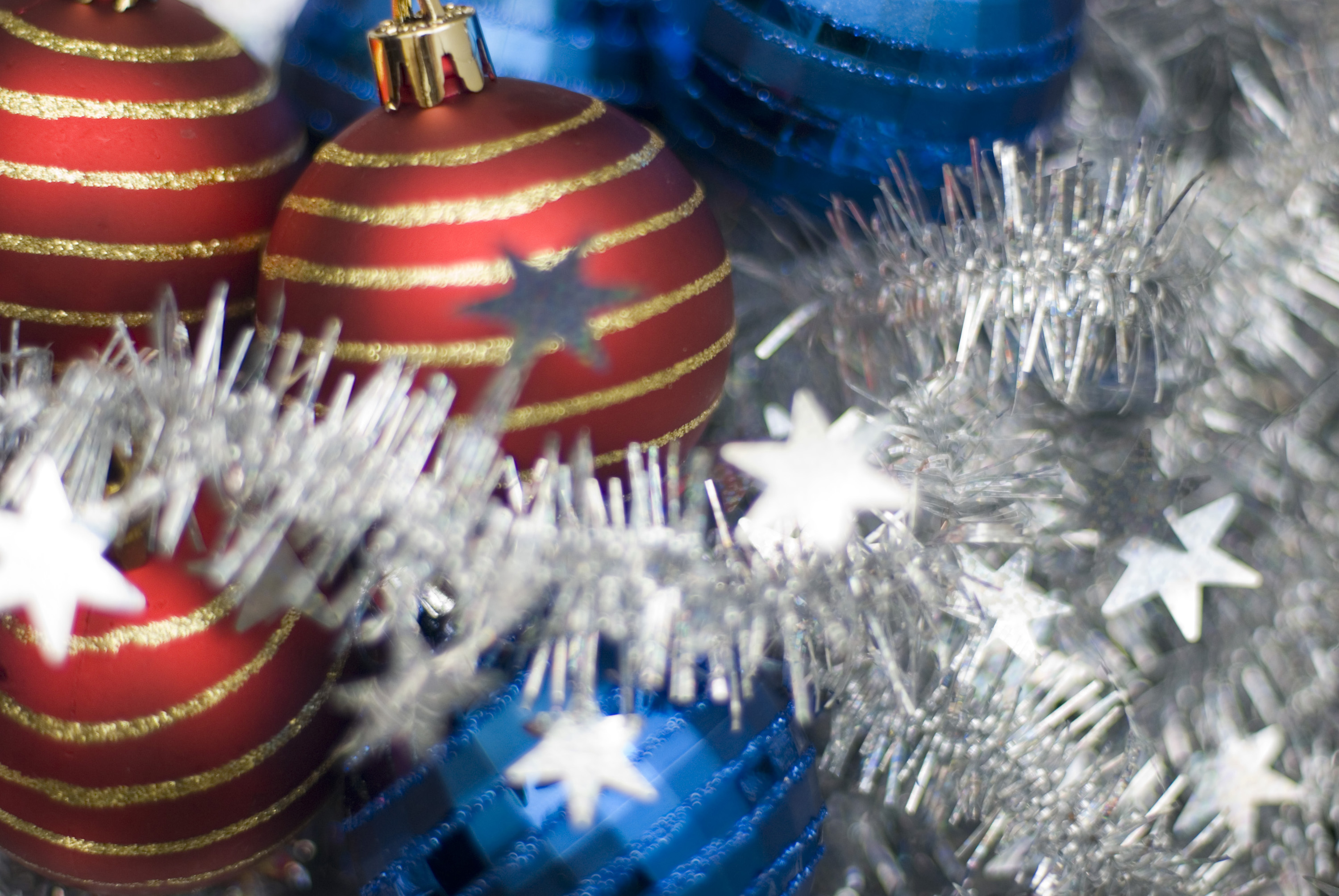 blue and red festive baubles on a background of tinsel, pictured with a narrow depth of field
