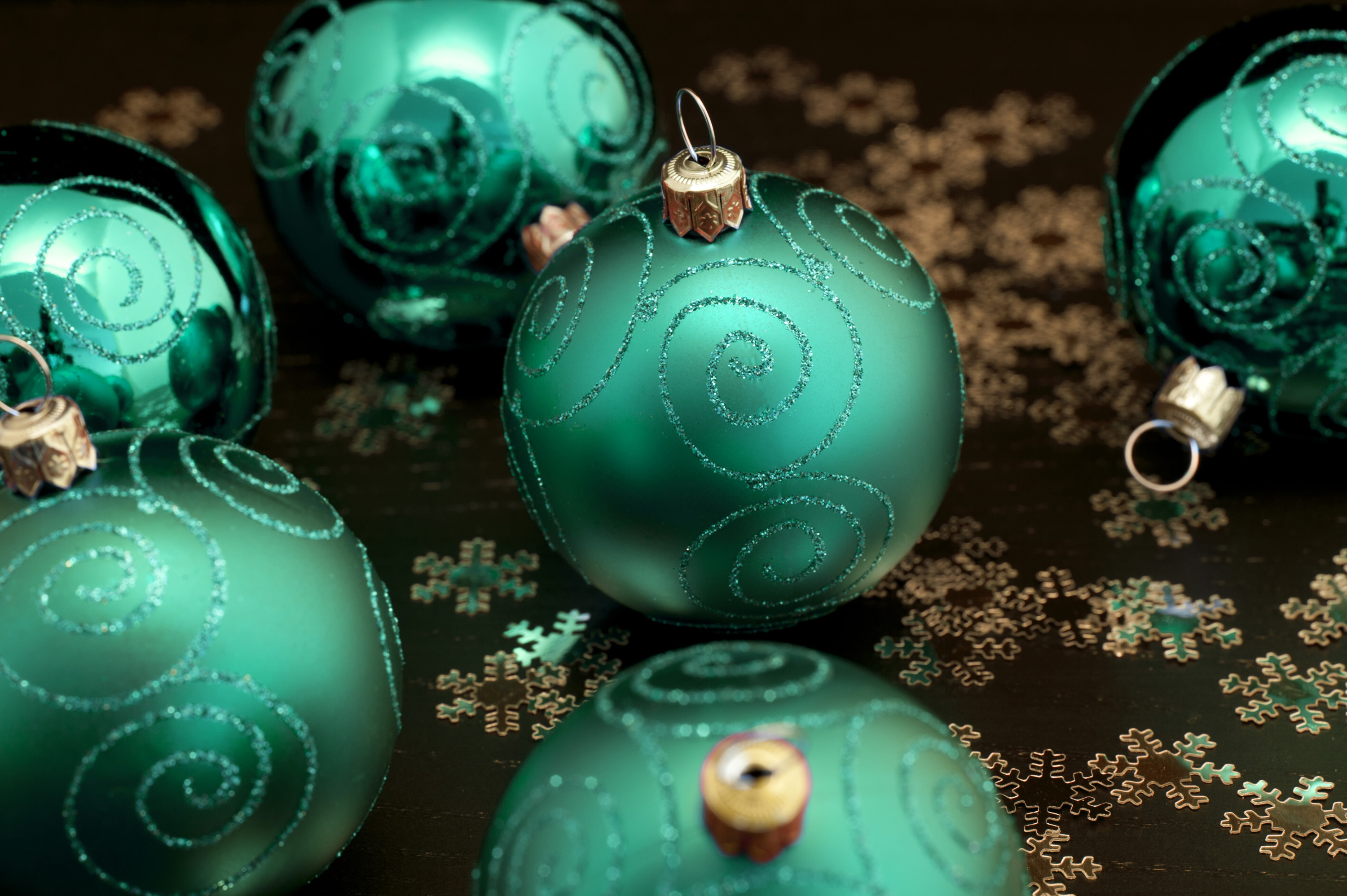 Emerald green Christmas balls patterned with glitter curlicues amongst scattered golden snowflakes