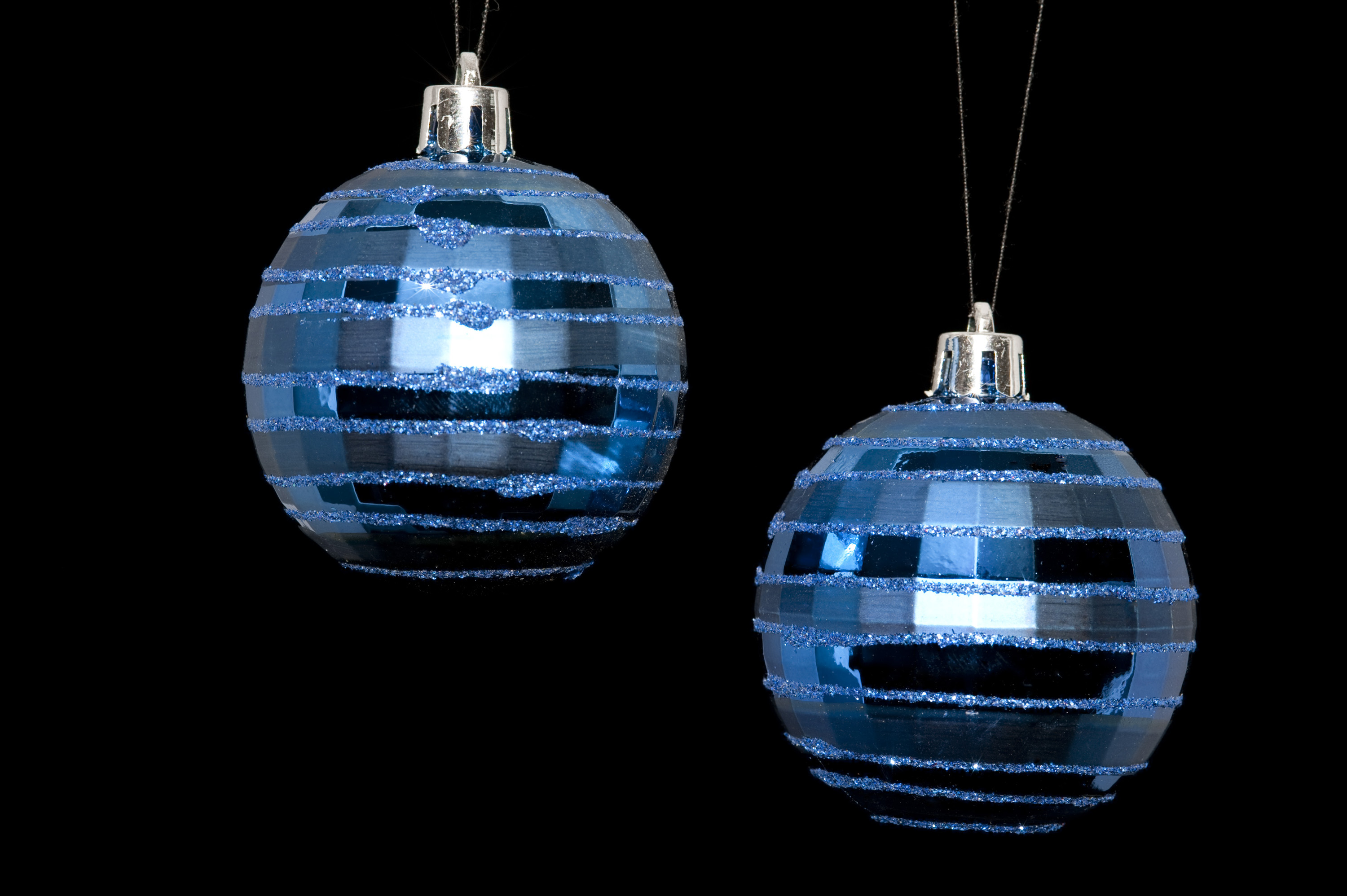 two hanging christmas baubles isolated on a black backdrop