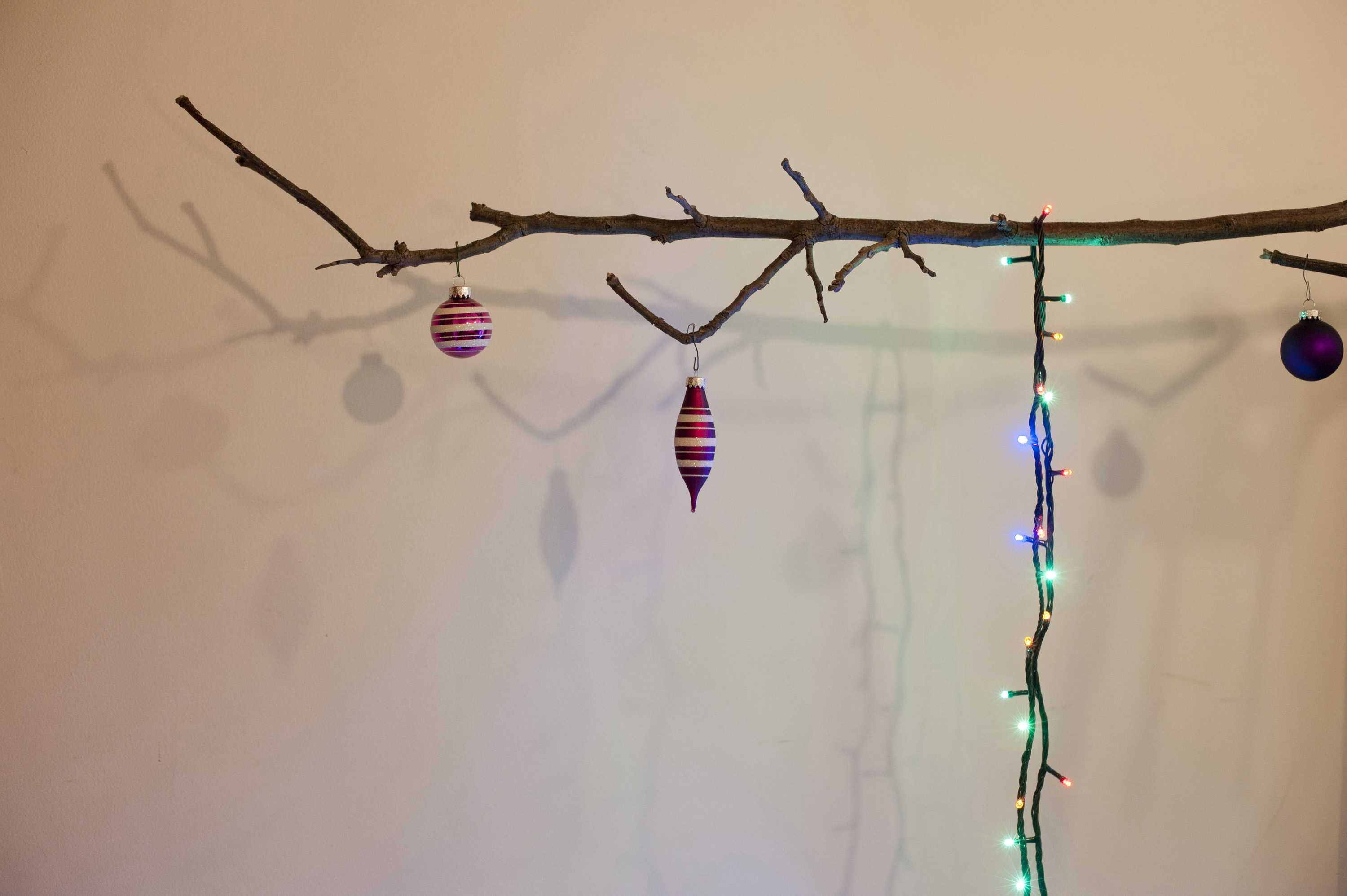 Christmas tree balls and garland hanging on leafless branch. Concept. White background