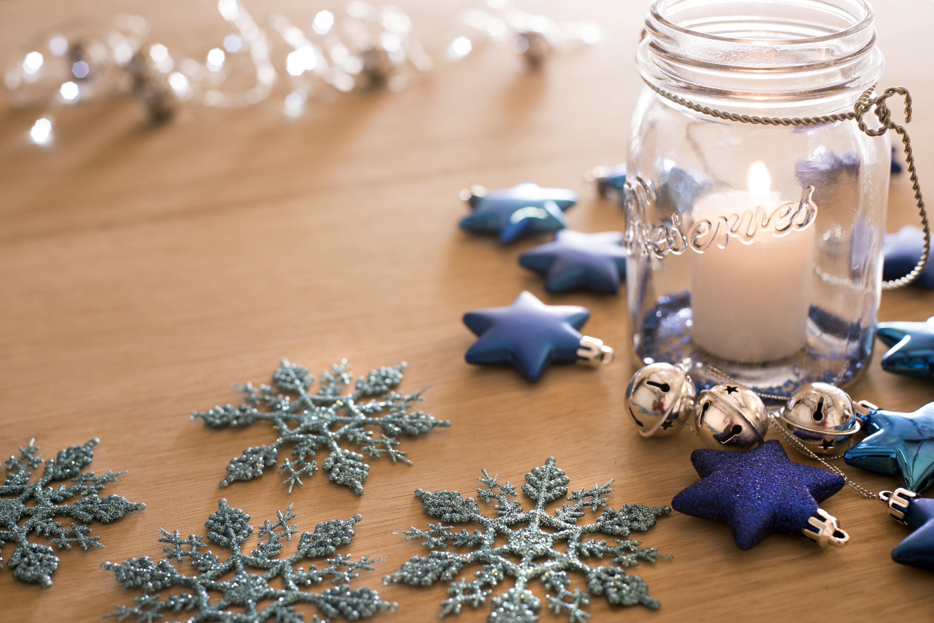 Still life of some decorative snowflakes and a jar with a lit candle inside