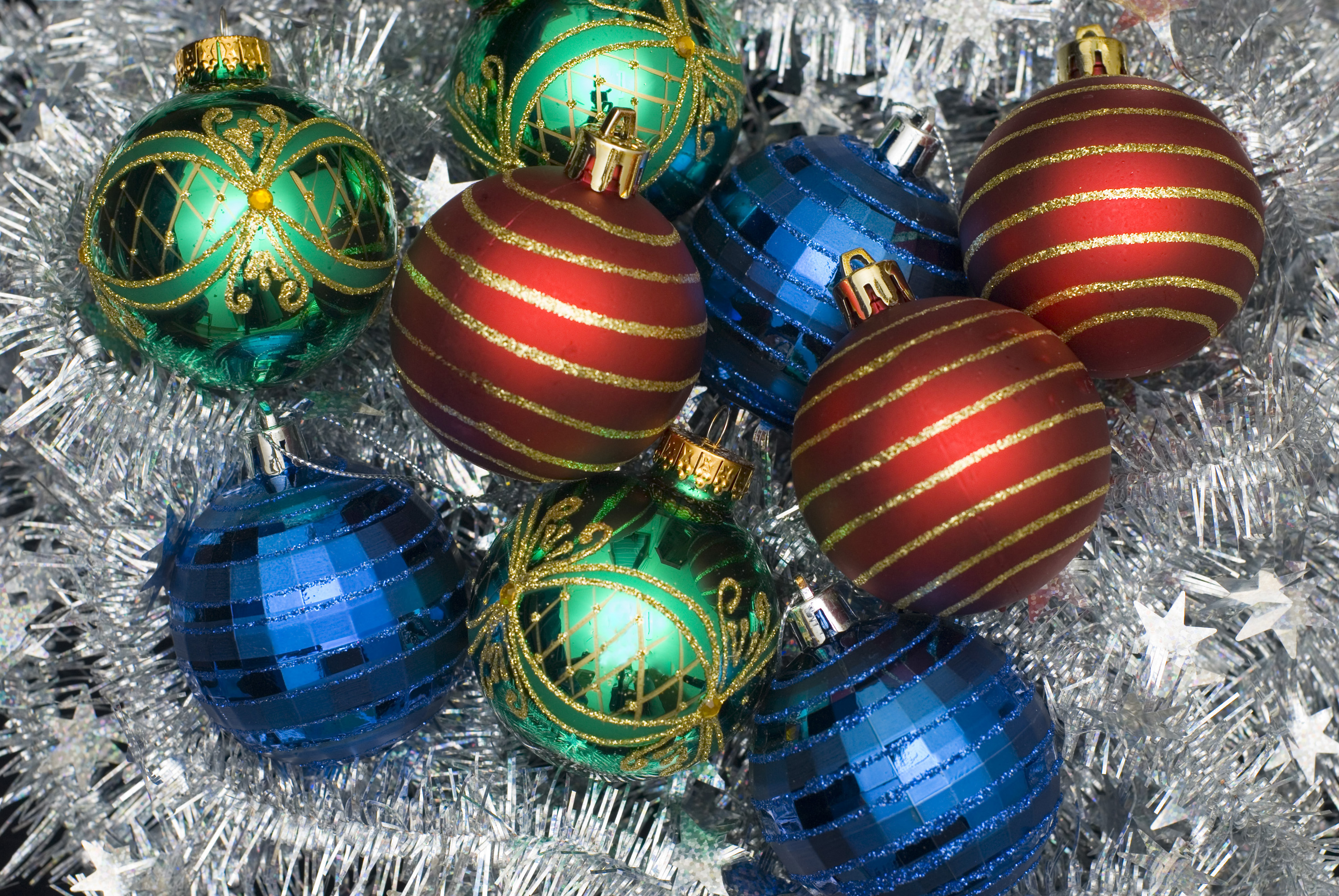 red green and blue christmas glass baubles on a background of silver tinsel