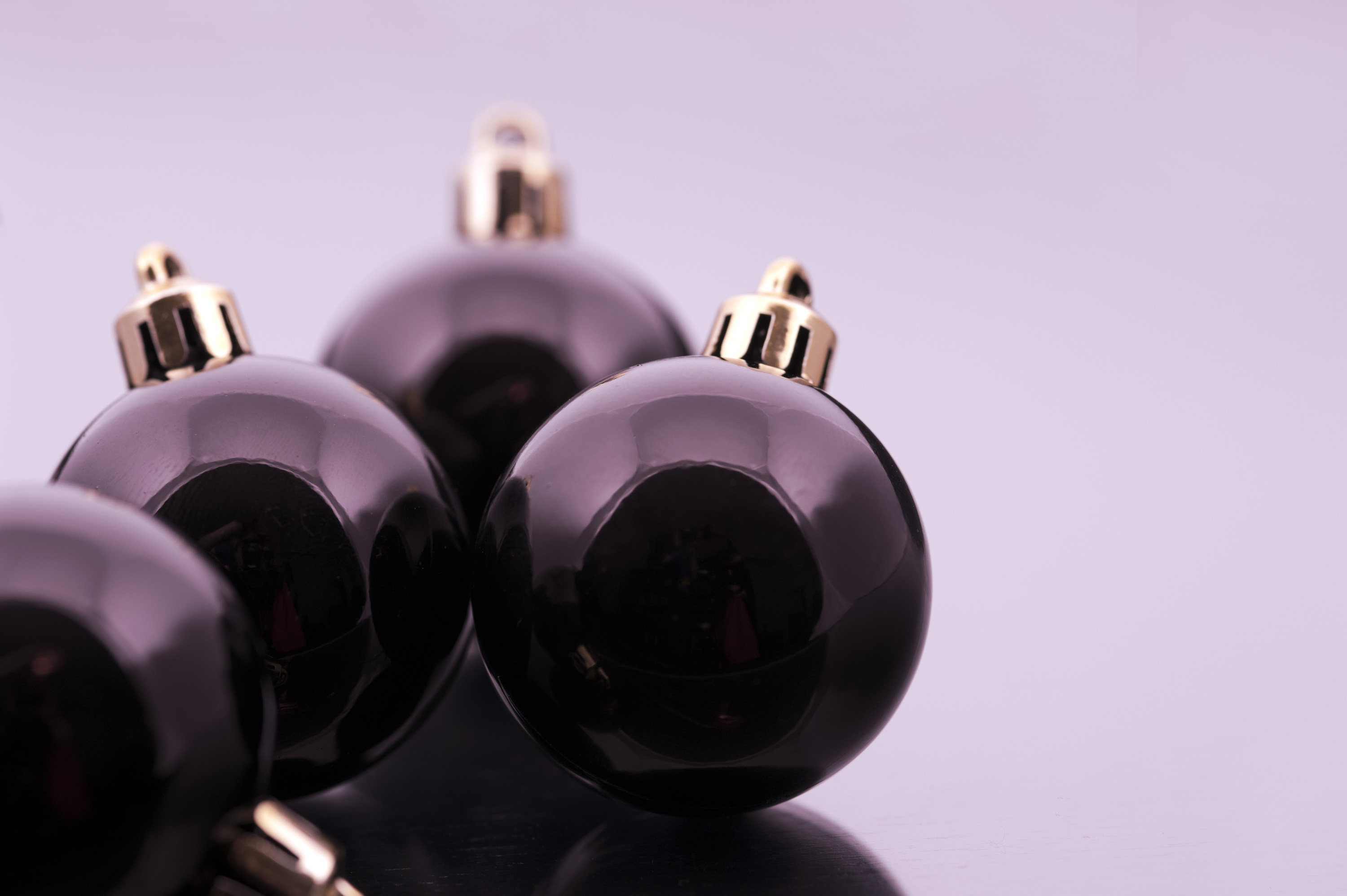 Black Christmas balls with reflections on a grey toned studio background with copyspace for your Xmas message