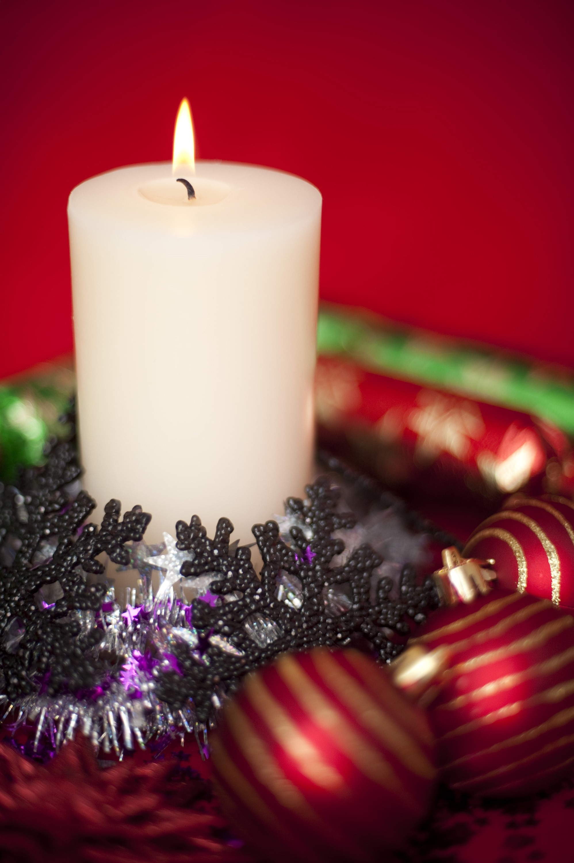 an arrangement of a burning christmas candle and various sparkling christmas decorations pictured with a narrow depth of field
