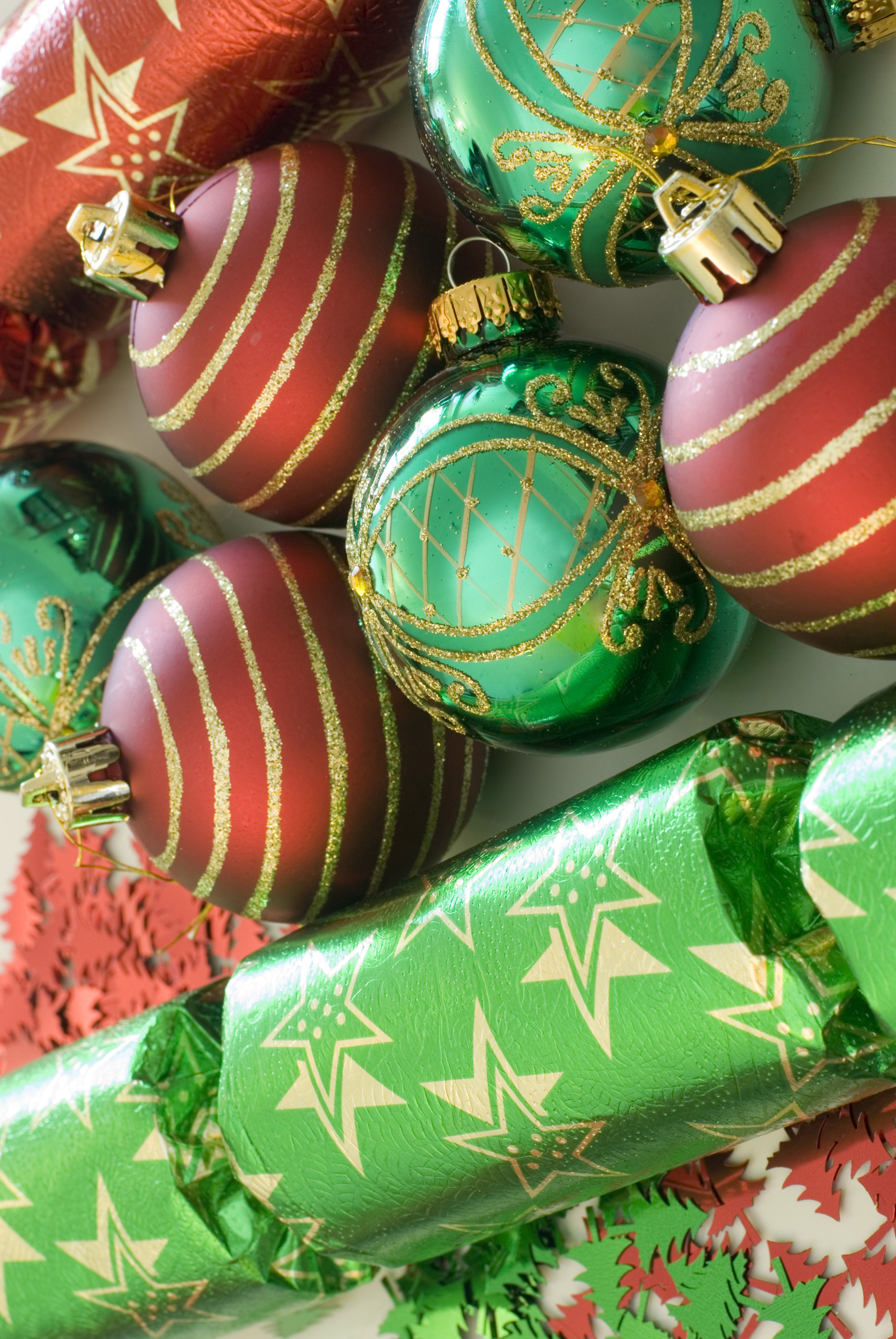 an assortment of red and green coloured christmas baubles and crackers