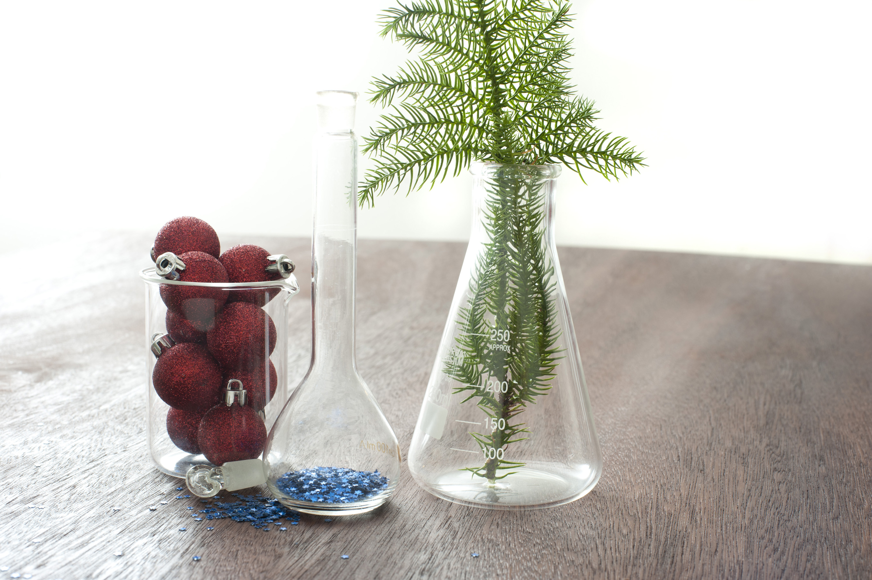 Christmas fir tree branch and decorations in chemisty glassware