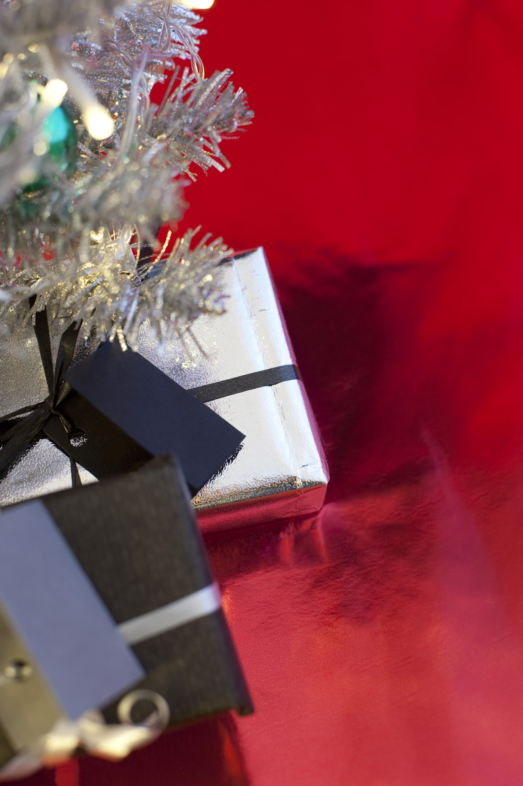 a background image with space for text featuring a silver christmas tree and presents at an oblique angle