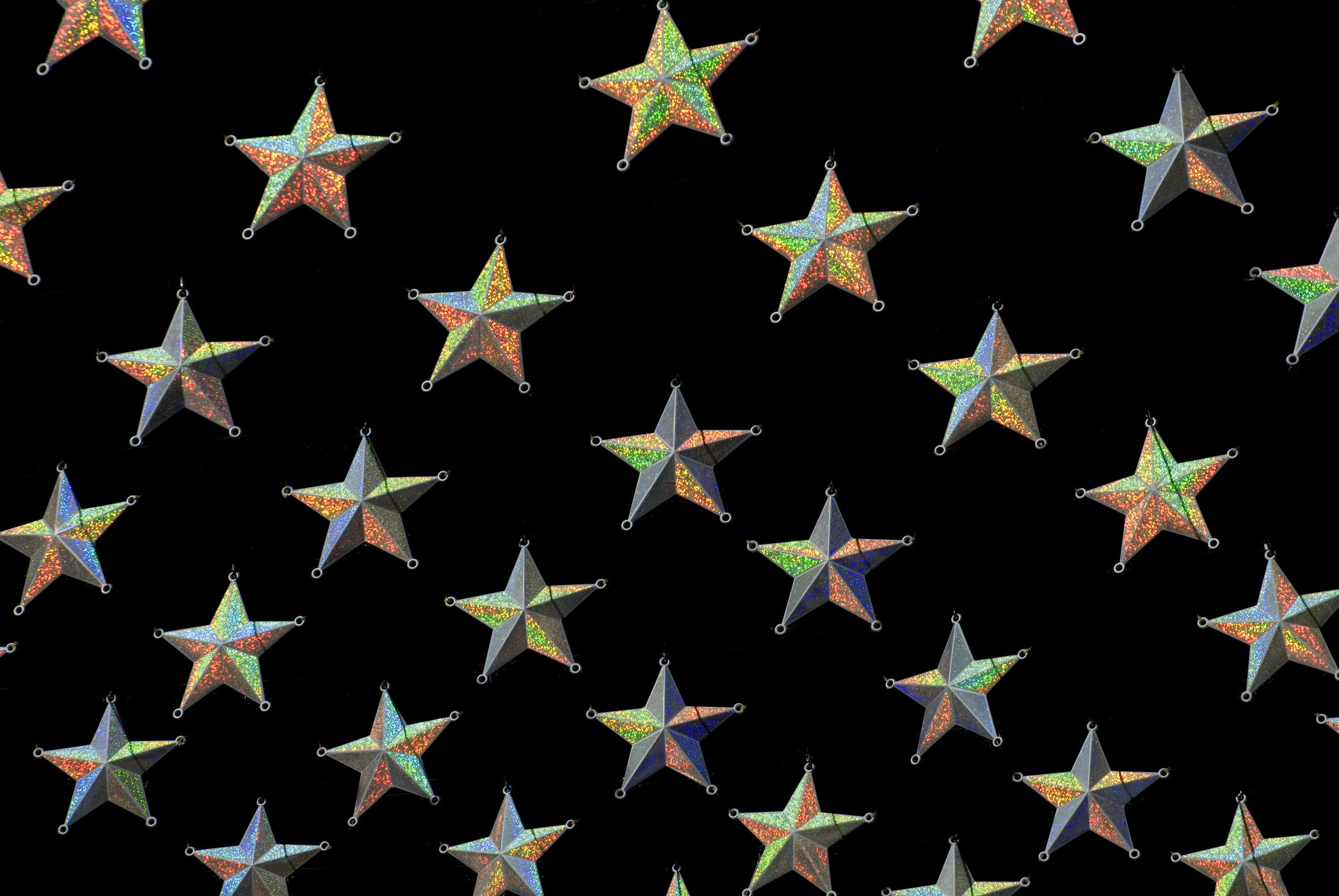 Gold star Christmas background with diagonal rows of stars on a black background