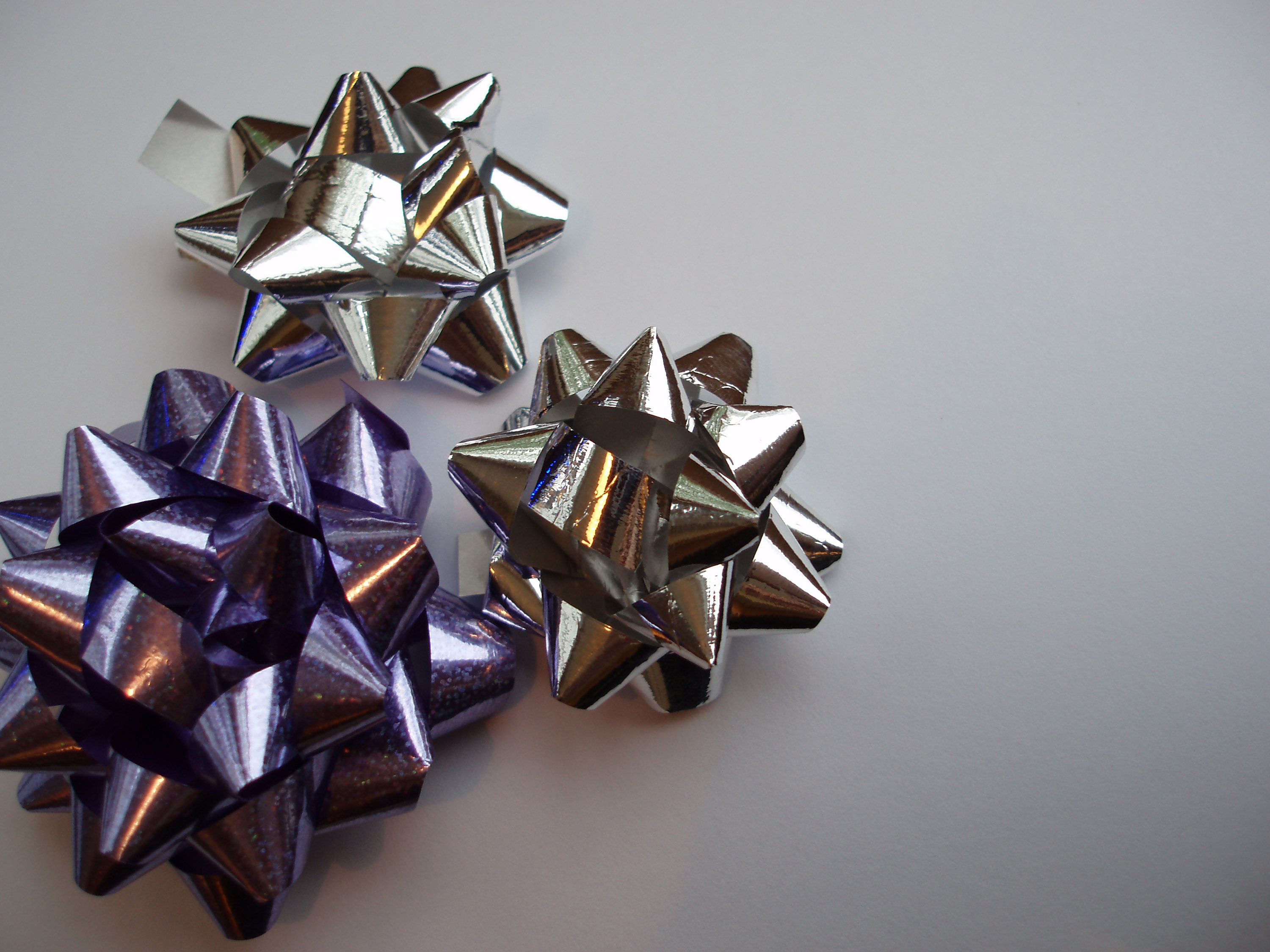 a decorative background of three reflective metalic wrapping bows