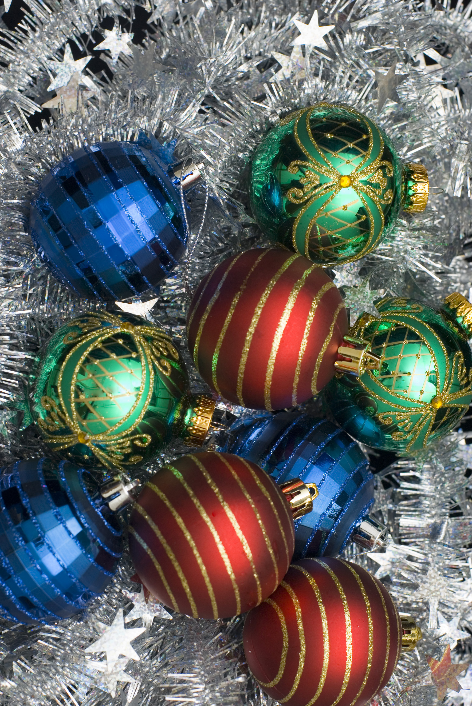 red green and blue christmas baubles on a background of tinsel creates a colorful christmas backdrop