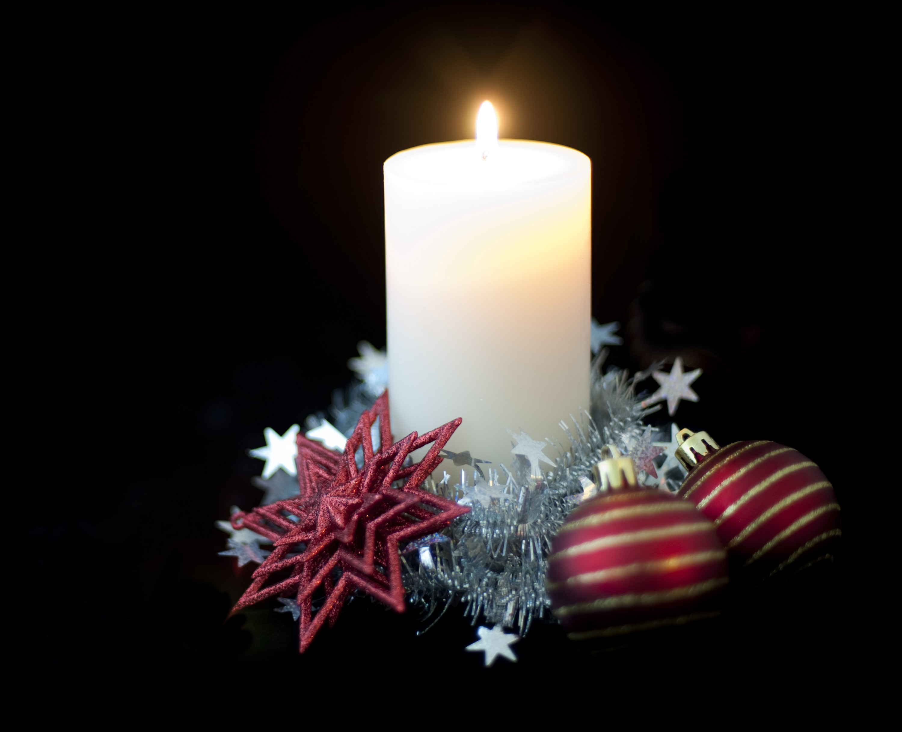 a soft focus candle and flame surrounded by christmas ornaments and tinsel