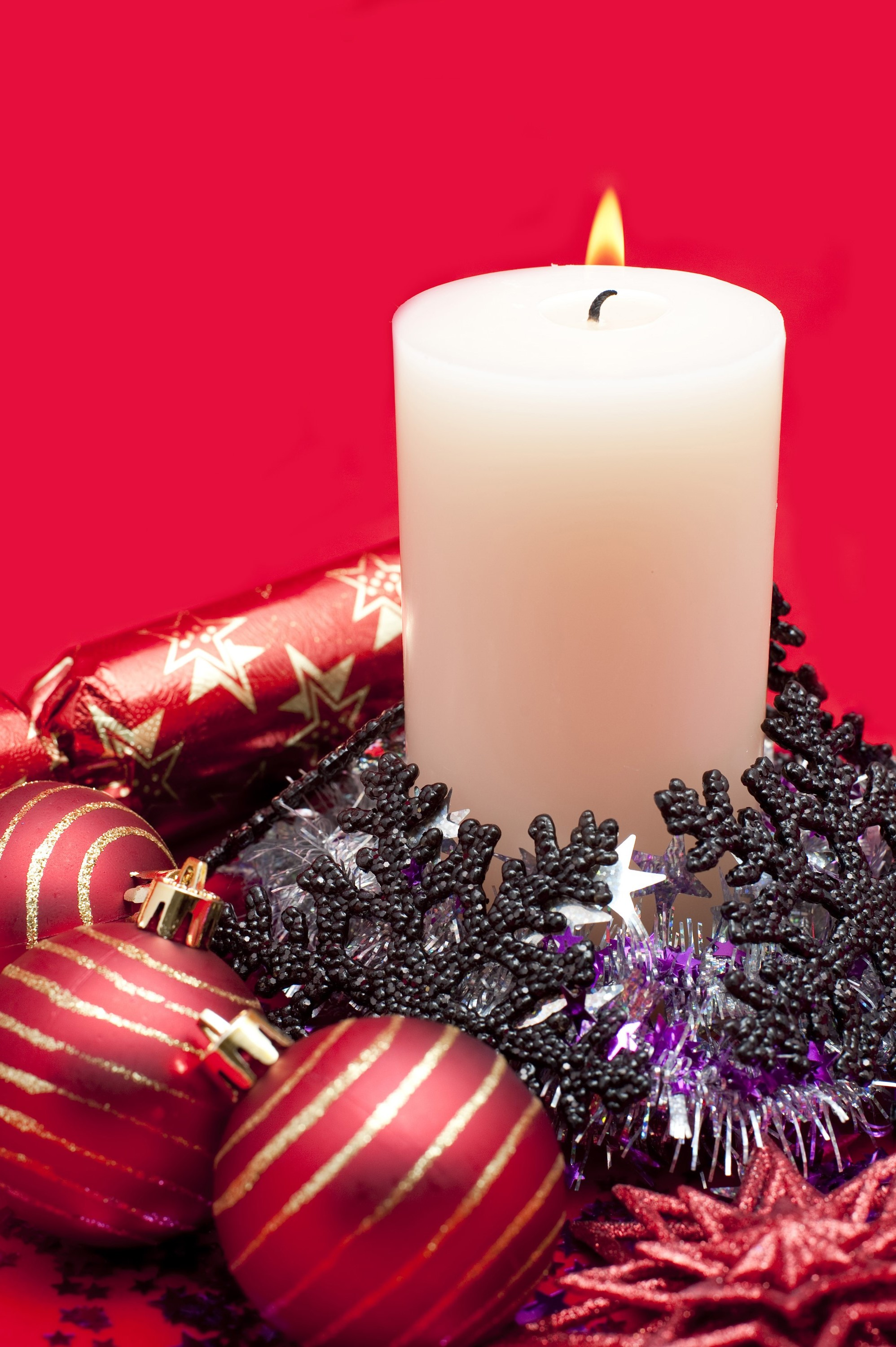 an arrangement of a lit christmas candle and various sparkling christmas decoration including baubles and tinsel