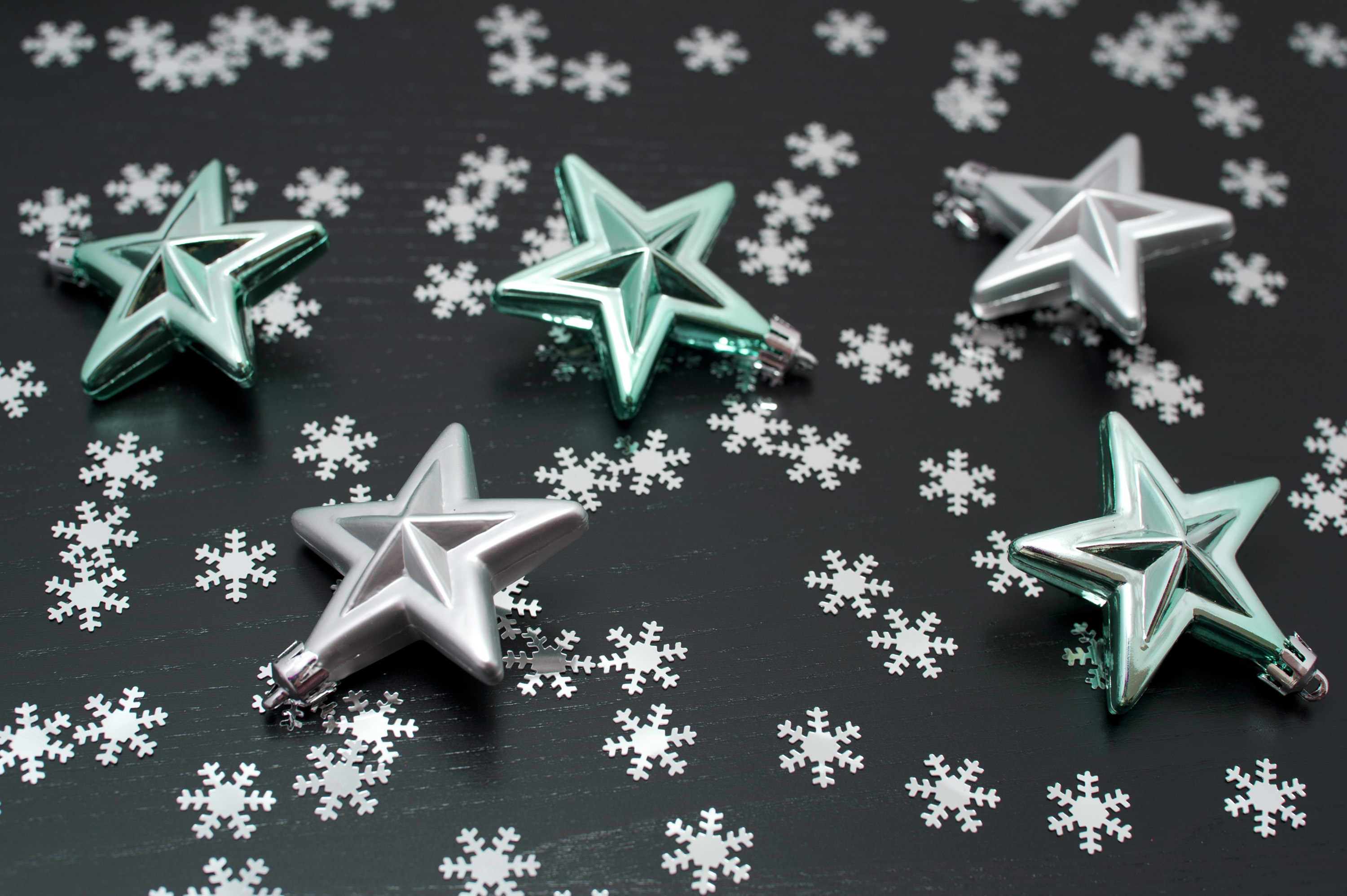 Randomly scattered festive stars and snowflakes on a black background for your seasons greetings