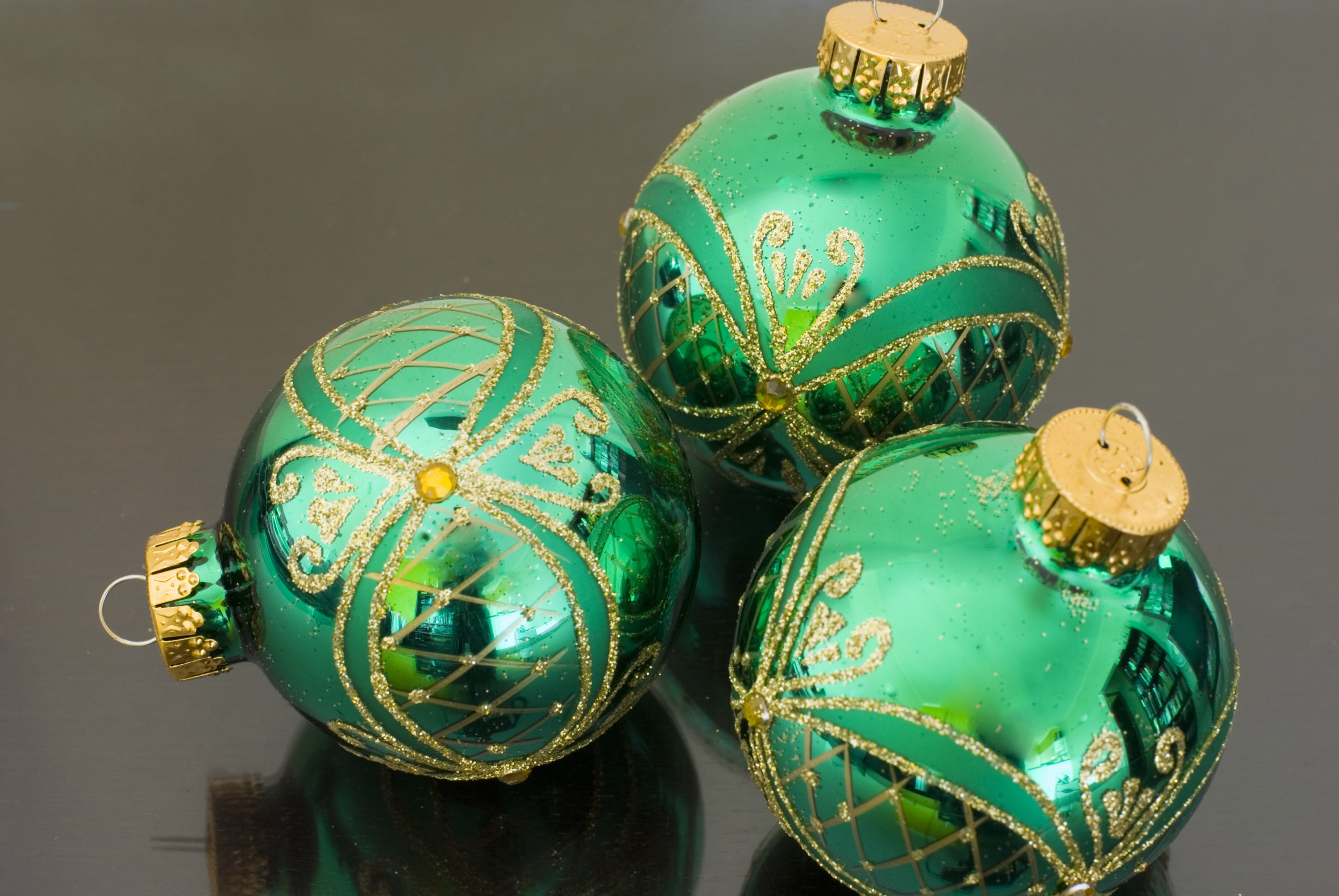 Three green reflective glass baubles on a dark background