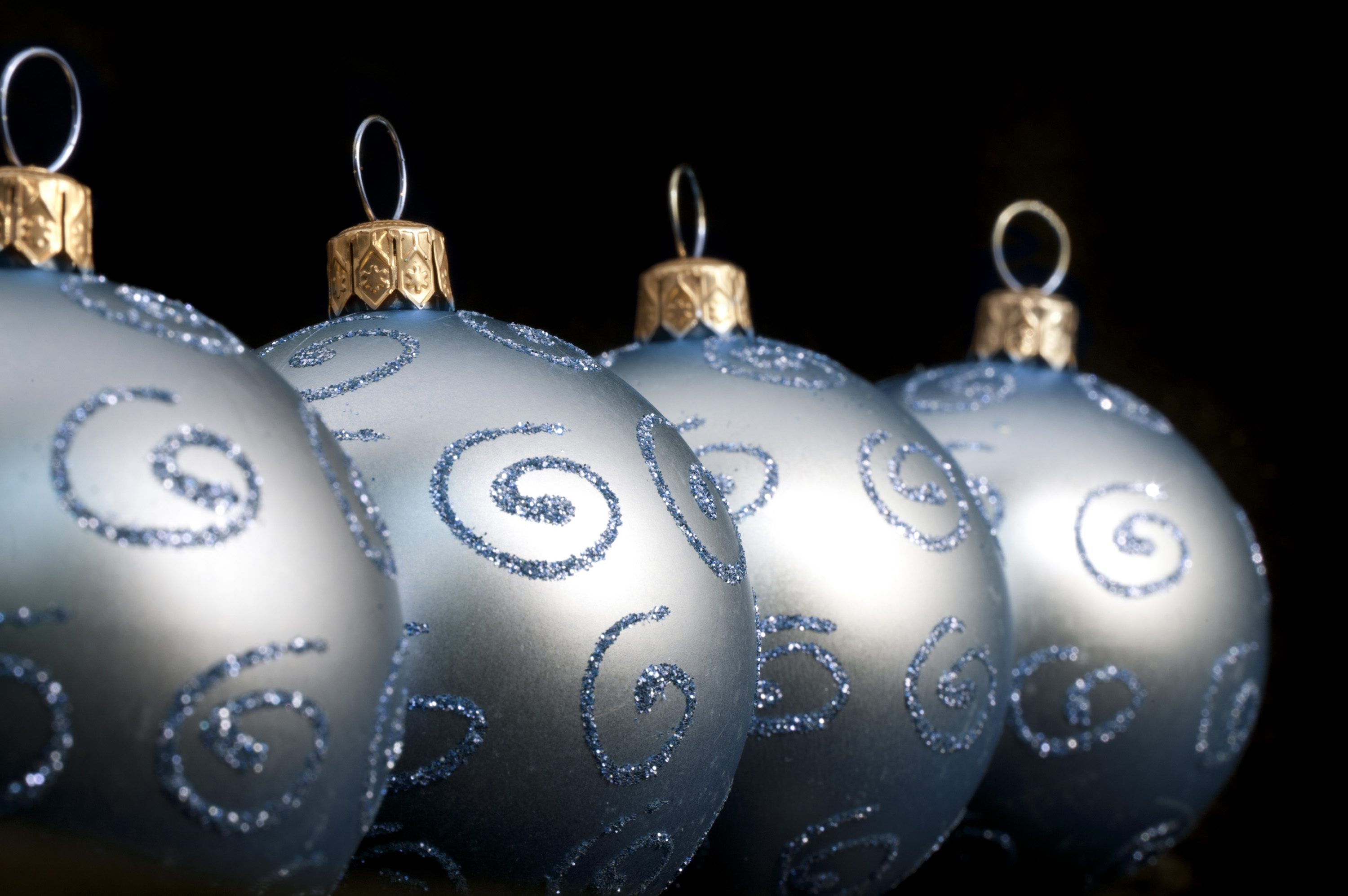 A receding row of pretty silvery blue Christmas balls decorated with glitter curlicues on a dark background