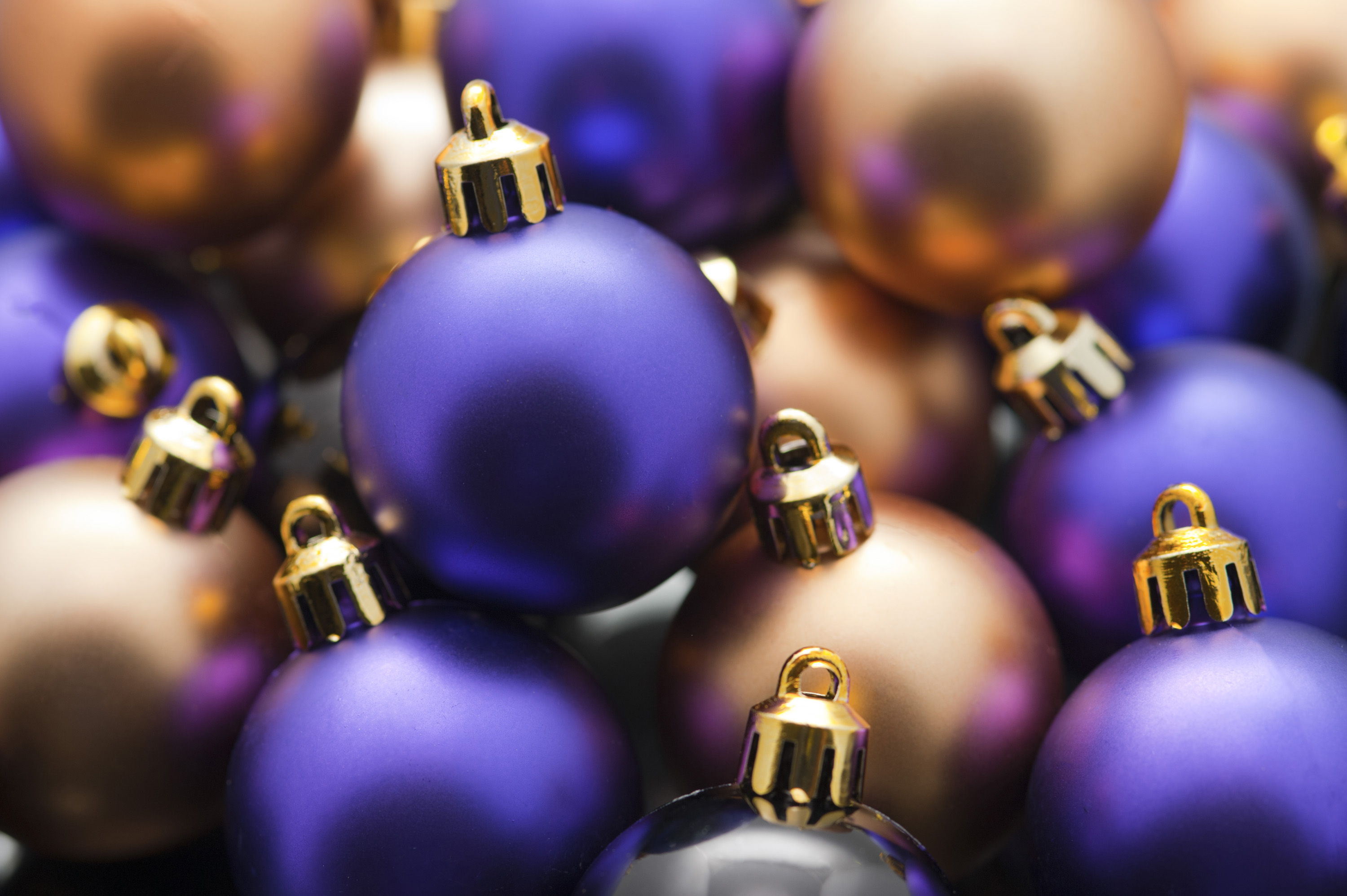 a narrow depth of field image of purple and gold coloured plain christmas baubles