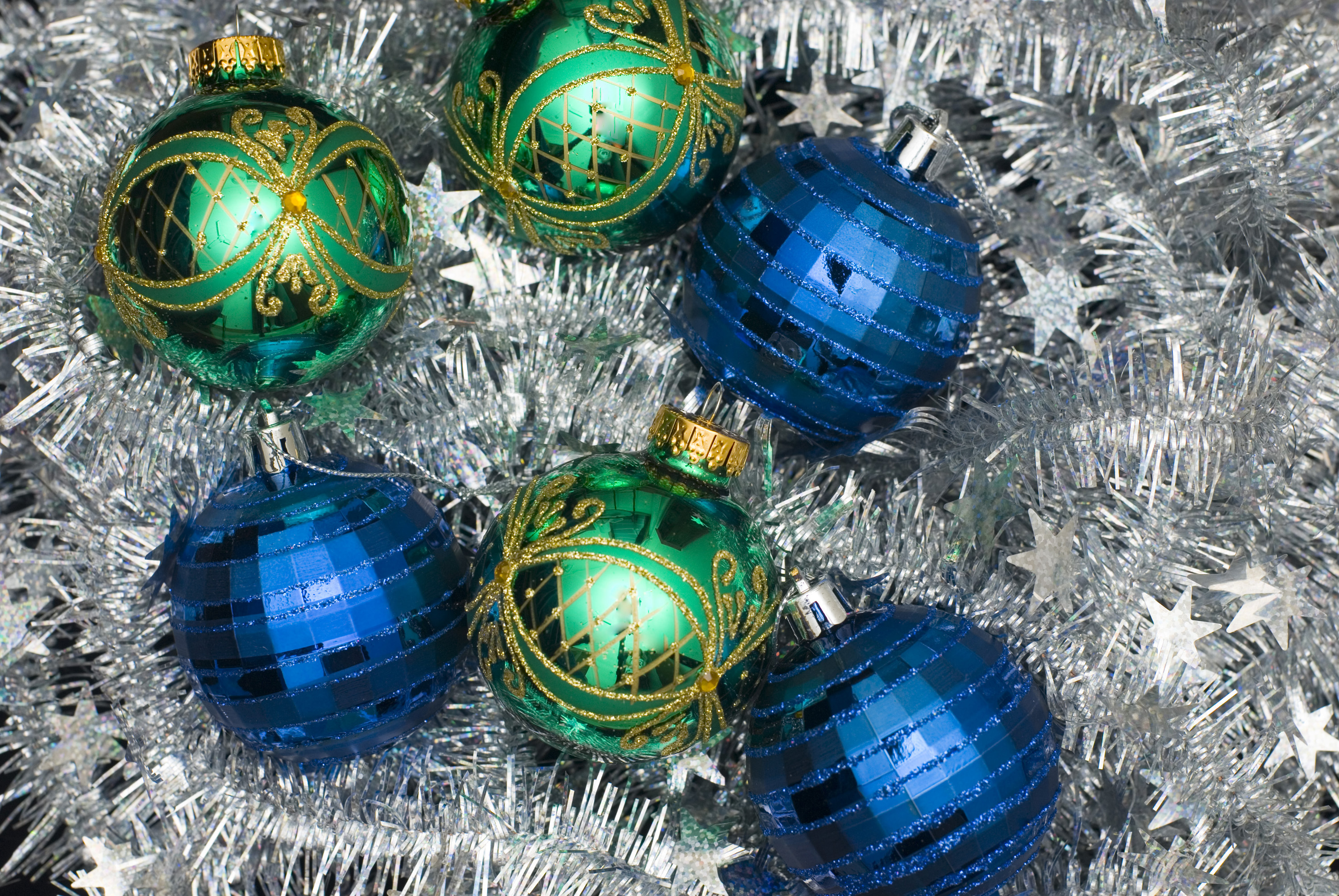 reflective and sparkling christmas balls on a silver tinsel backdrop