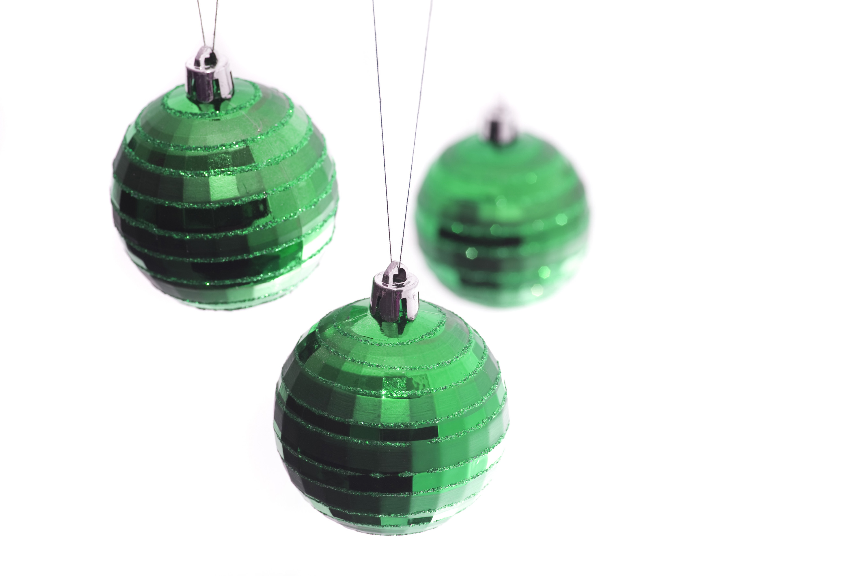 a trio of hanging green christmas tree baubles