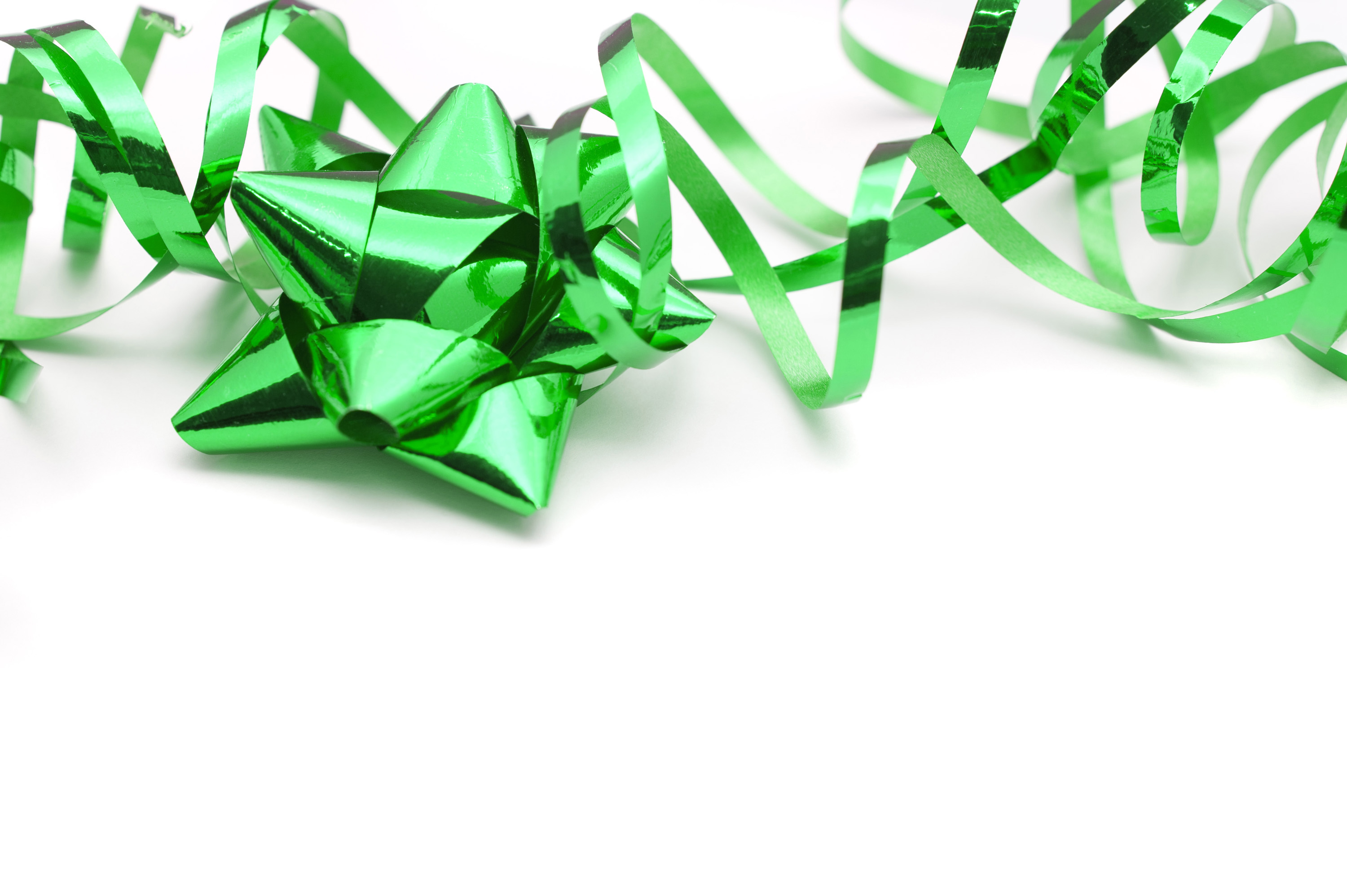 Festive metallic green bow and twirled ribbon for gift wrapping Christmas gifts or presents for a special occasion on a white background with copyspace