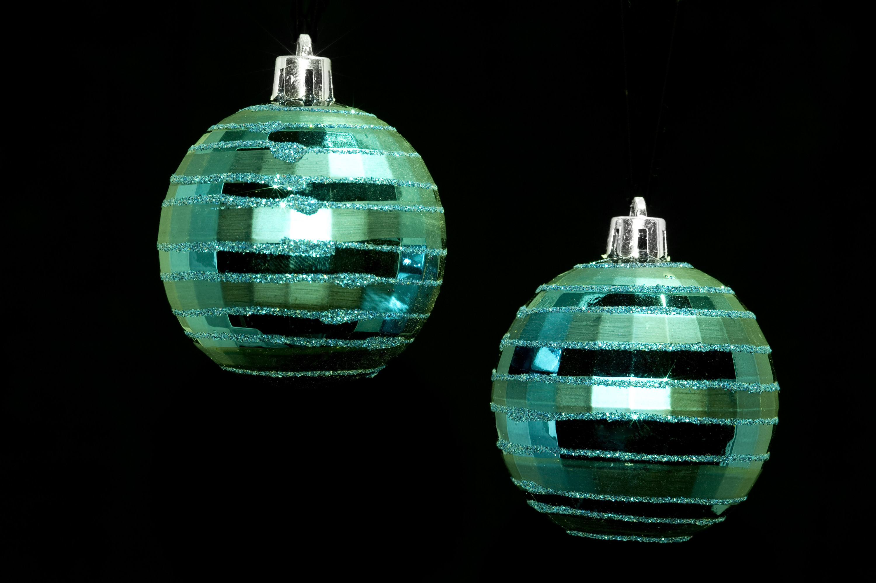 two hanging green christmas baubles isolated on a black backdrop