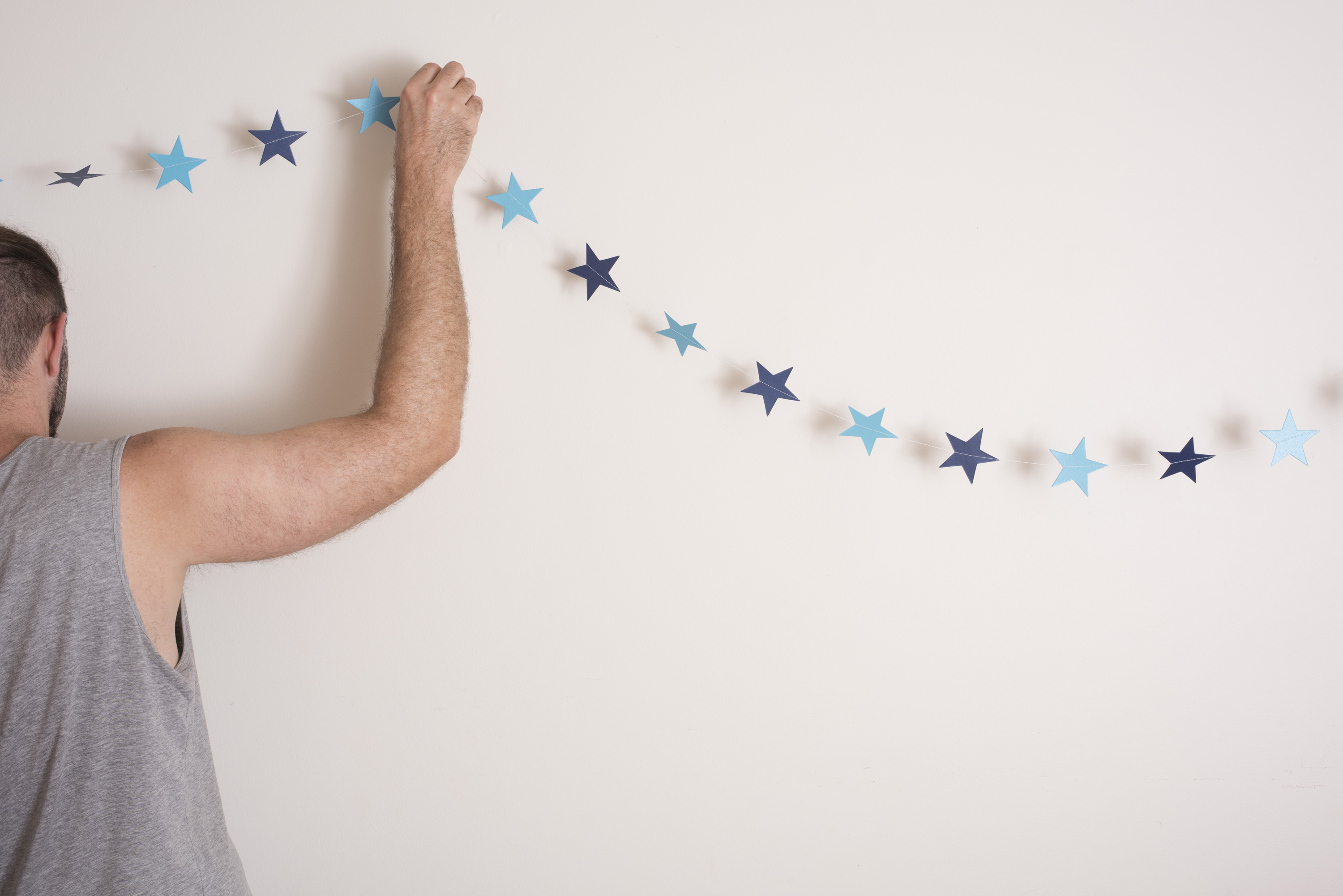Man hanging simple Christmas bunting with a single string of blue paper stars on the wall of his house for a minimalist celebration