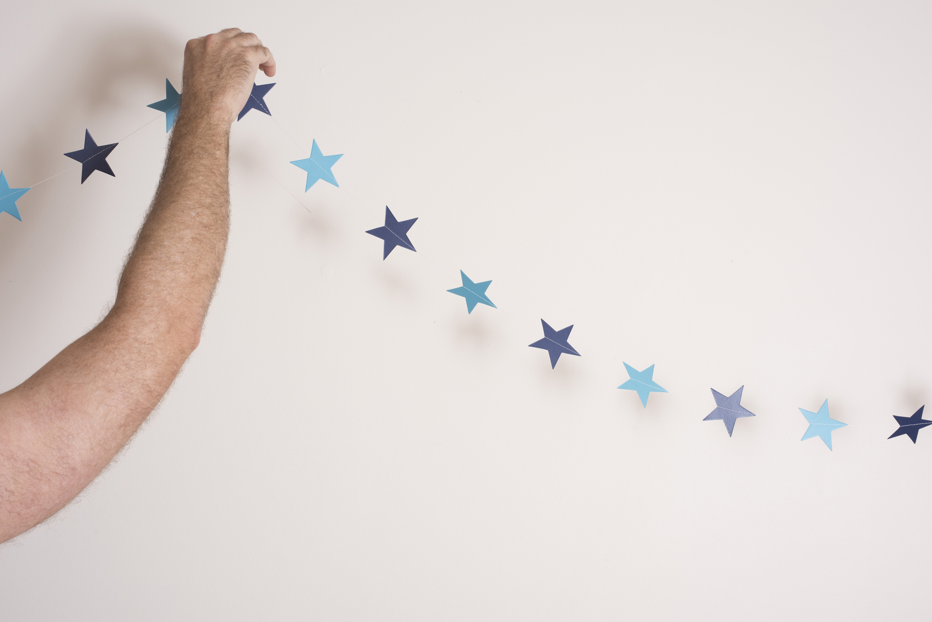 Man hanging decorative blue star bunting for Christmas at home against a white wall with copy space, close up of his bare arm