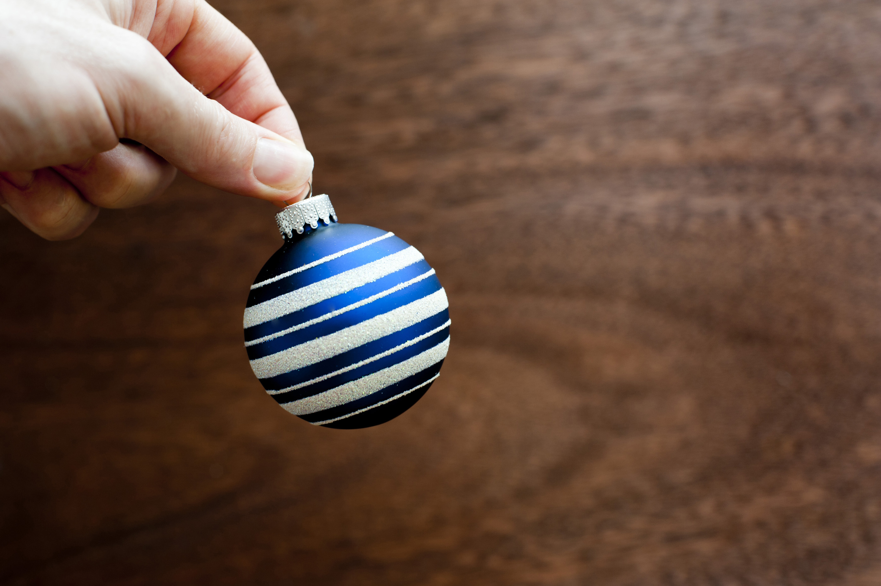 holding Christmas glass bauble on wooden background