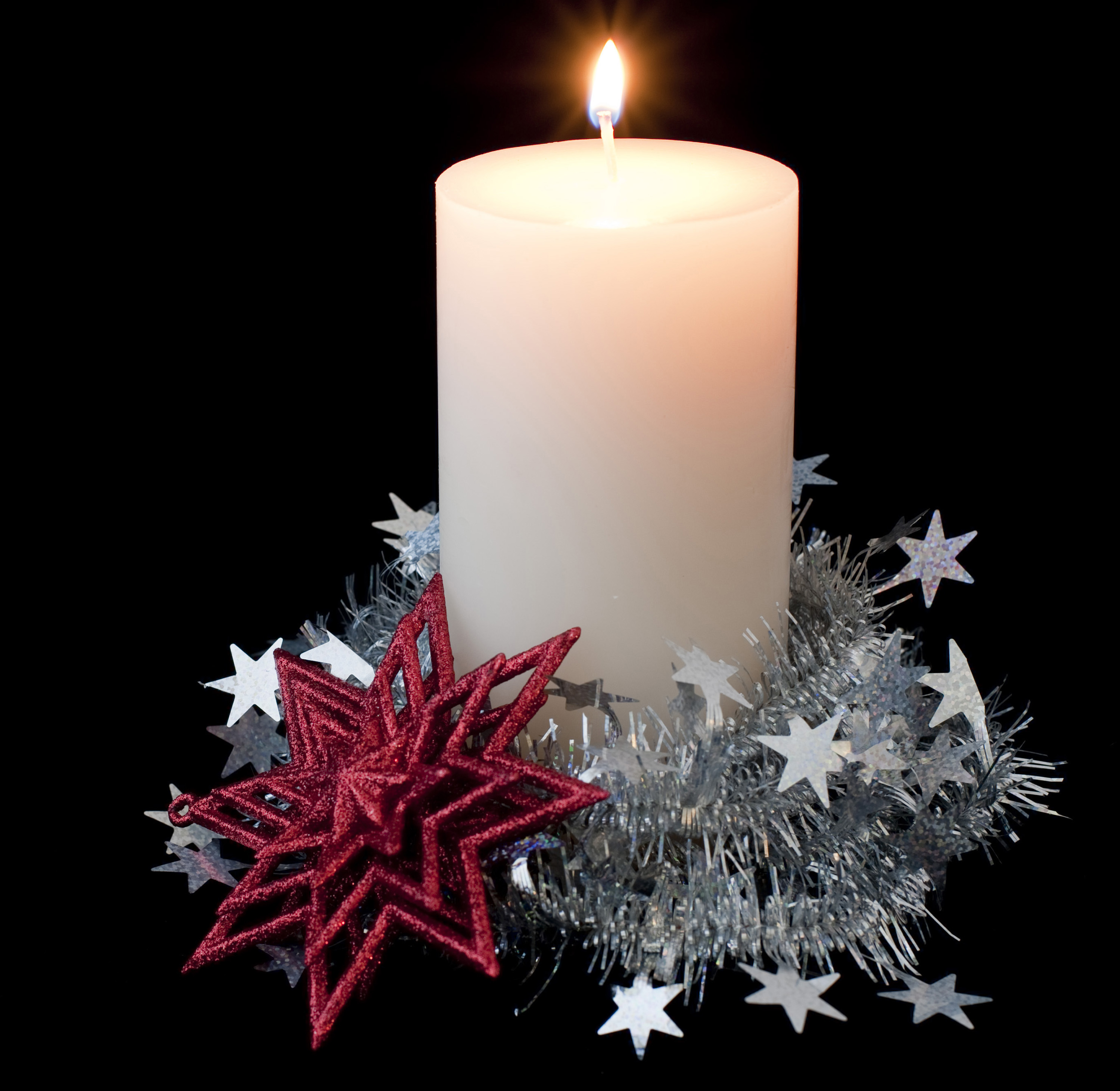 a burning pillar candle surrounded by seasonal decorations
