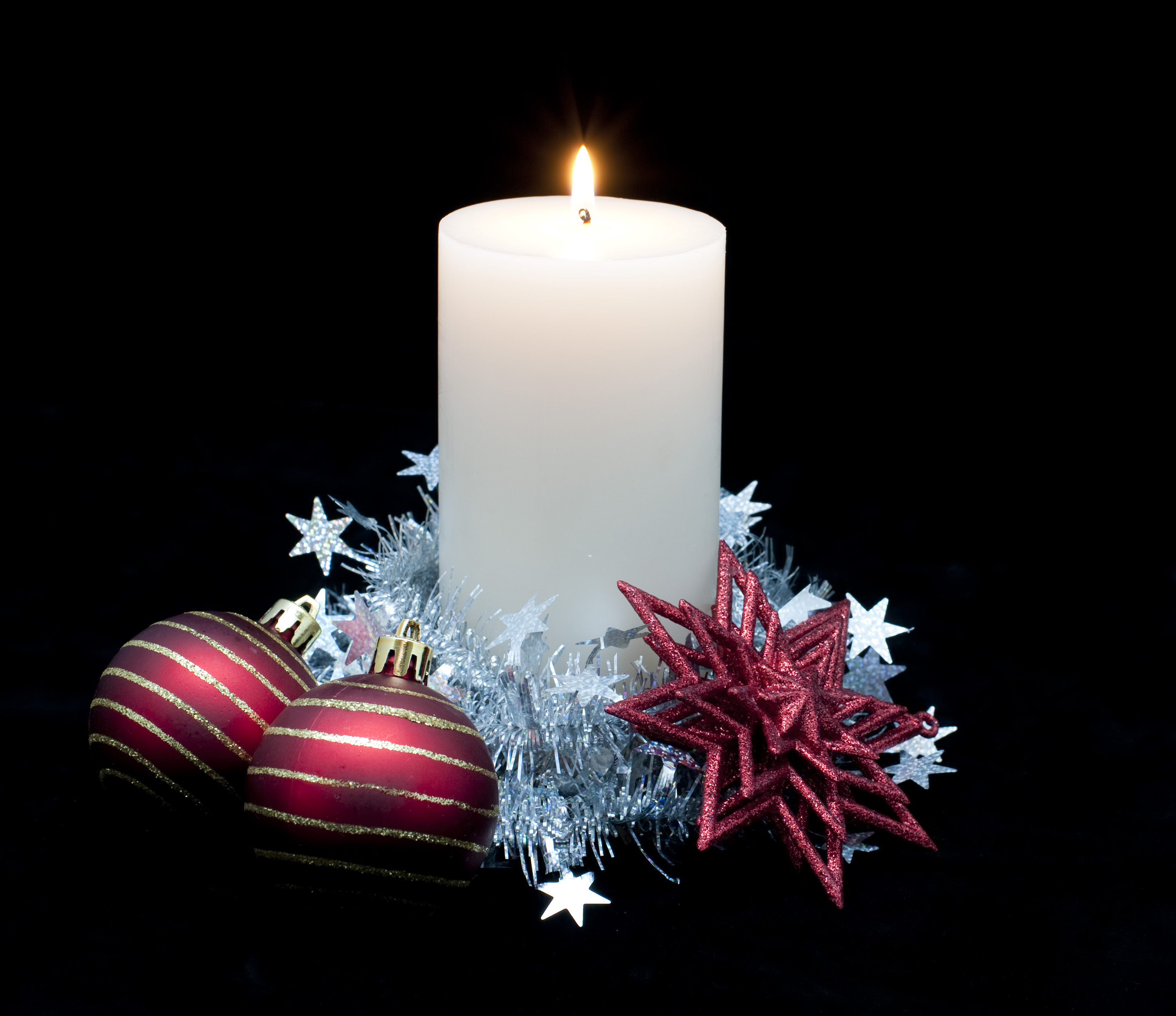a large pillar candle surrounded by seasonal decorations on a black backdrop