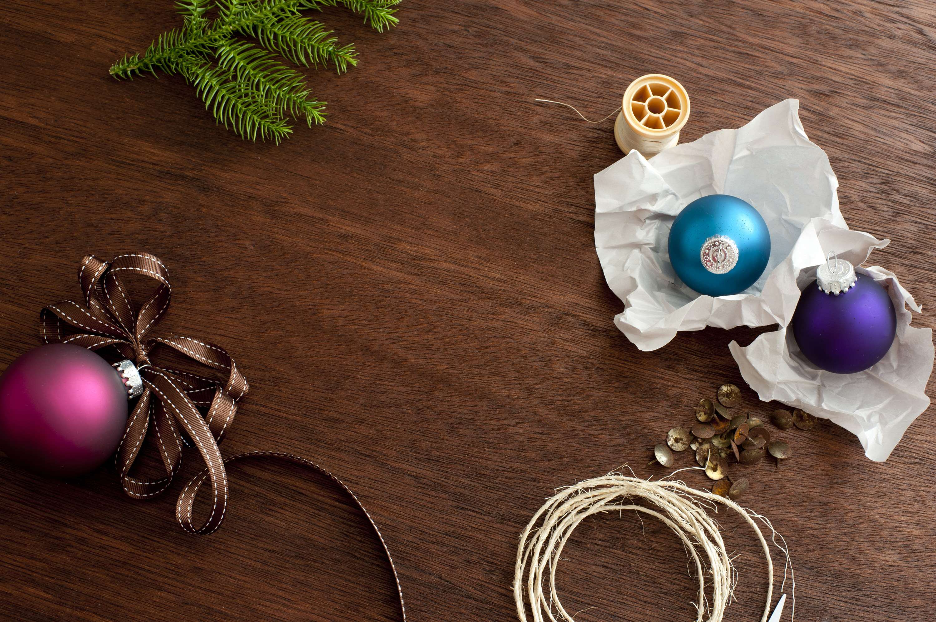 Christmas baubles and string on wooden surface