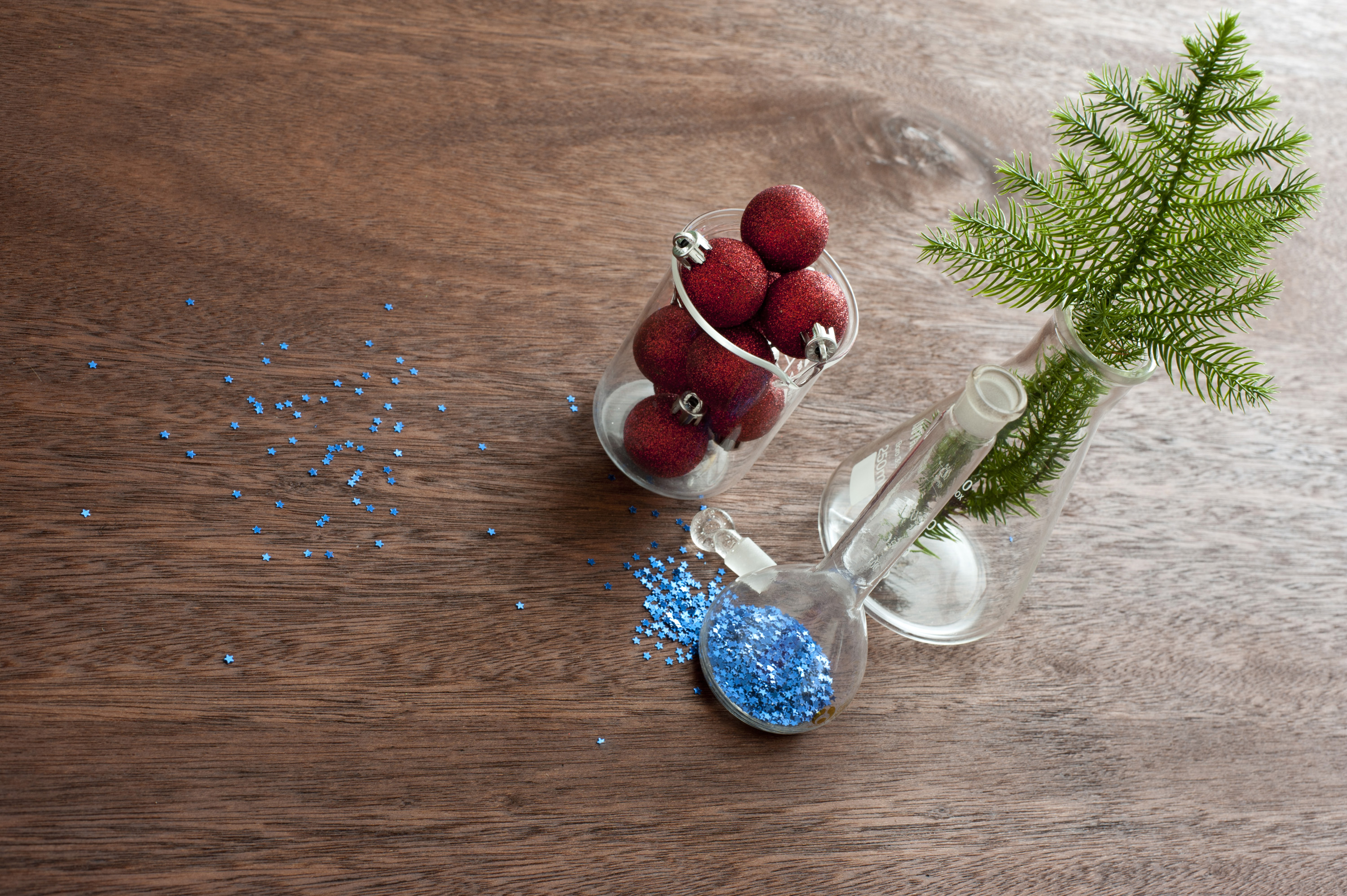 Christmas decoration, blue sparkles and fir branch on wooden table in glass containers, making christmas concept