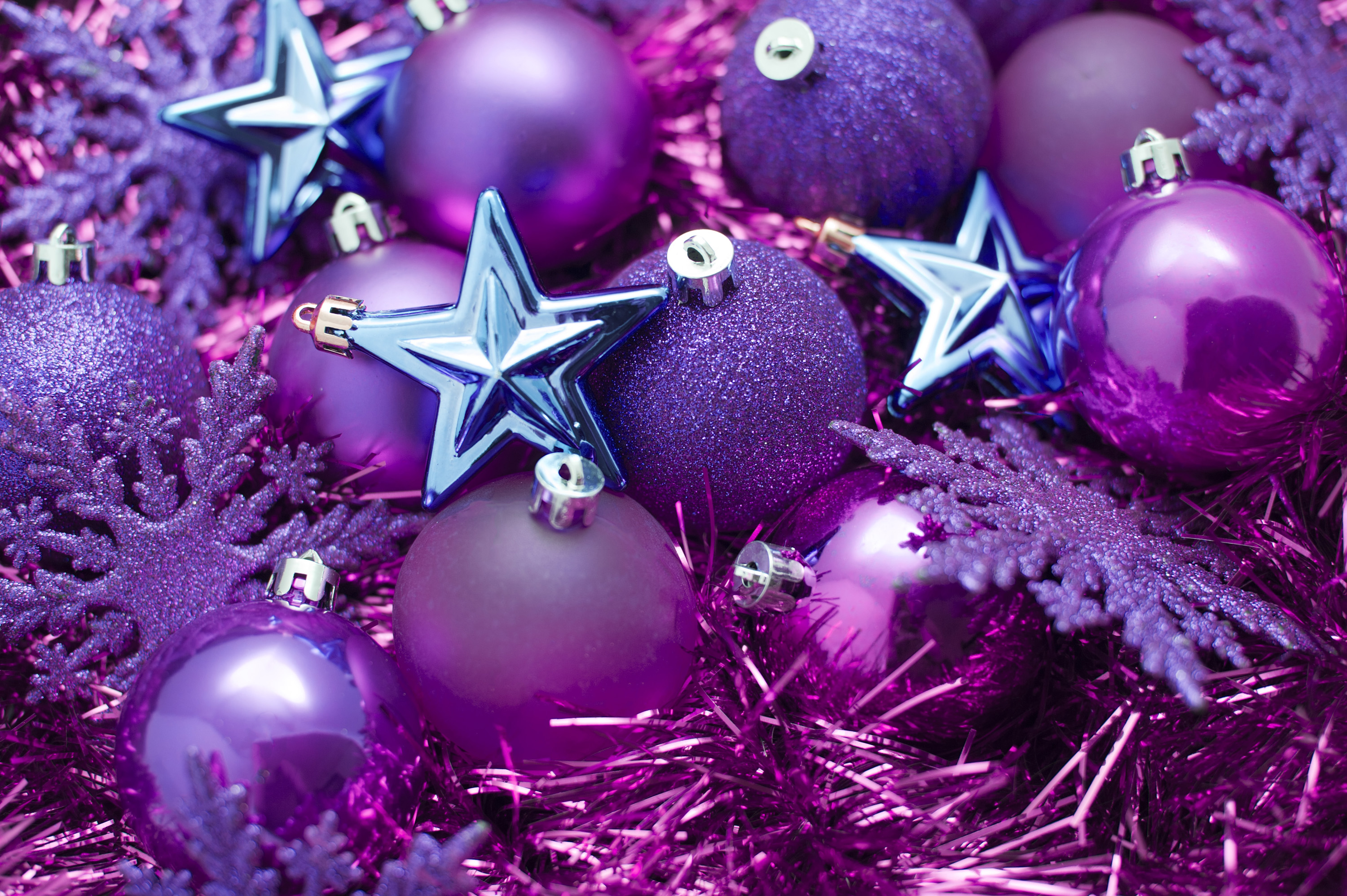 An assortment of different purple and pink Christmas decorations including baubles, snowflakes, stars and tinsel