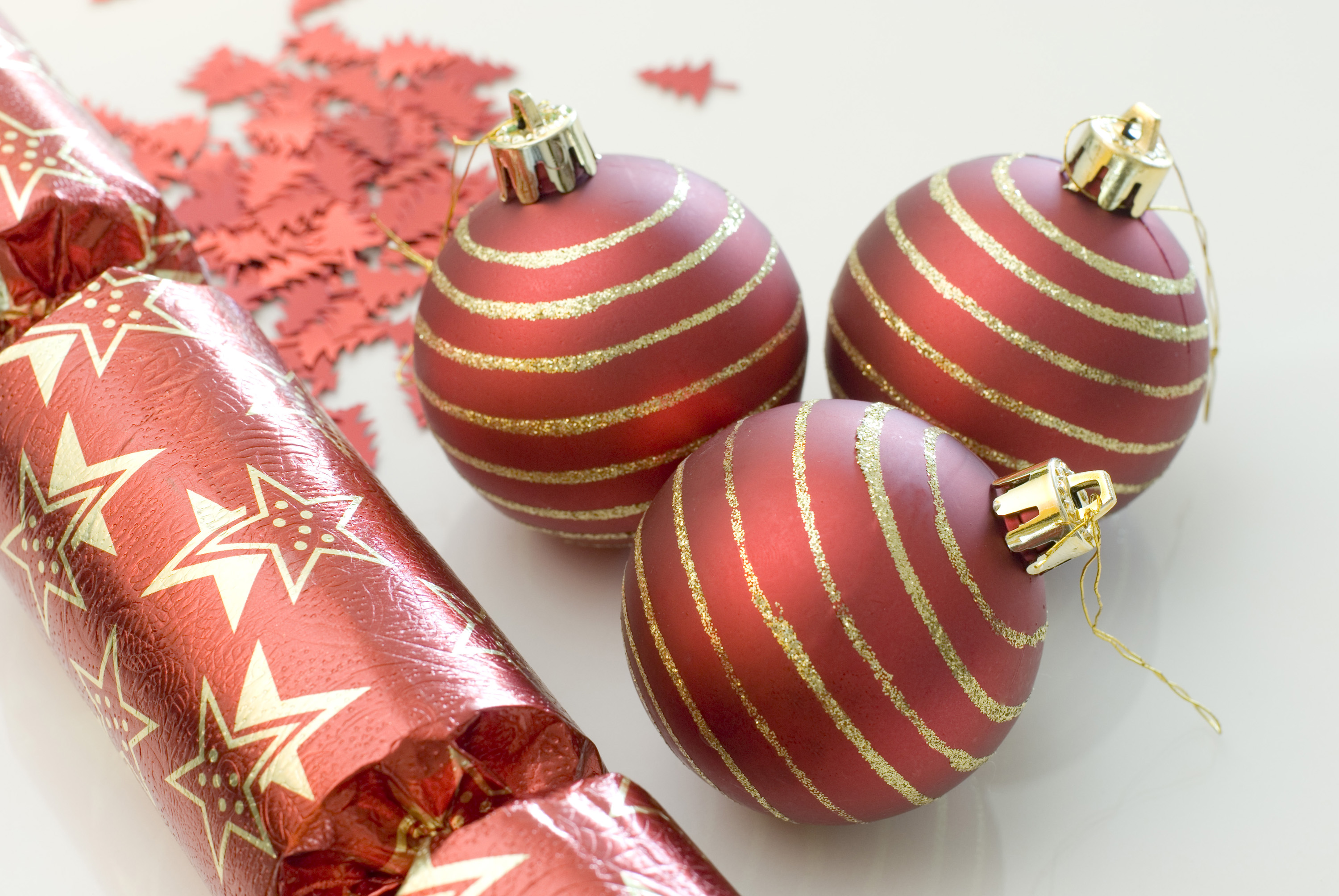 a selection of red coloured christmas balls, crackers and confetti glitter