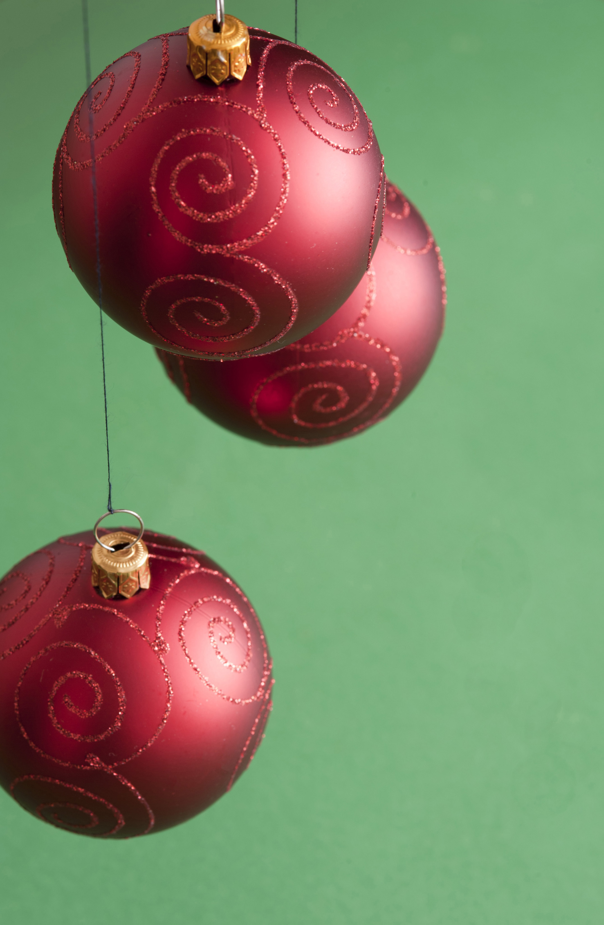 Three Christmas balls hanging on green background