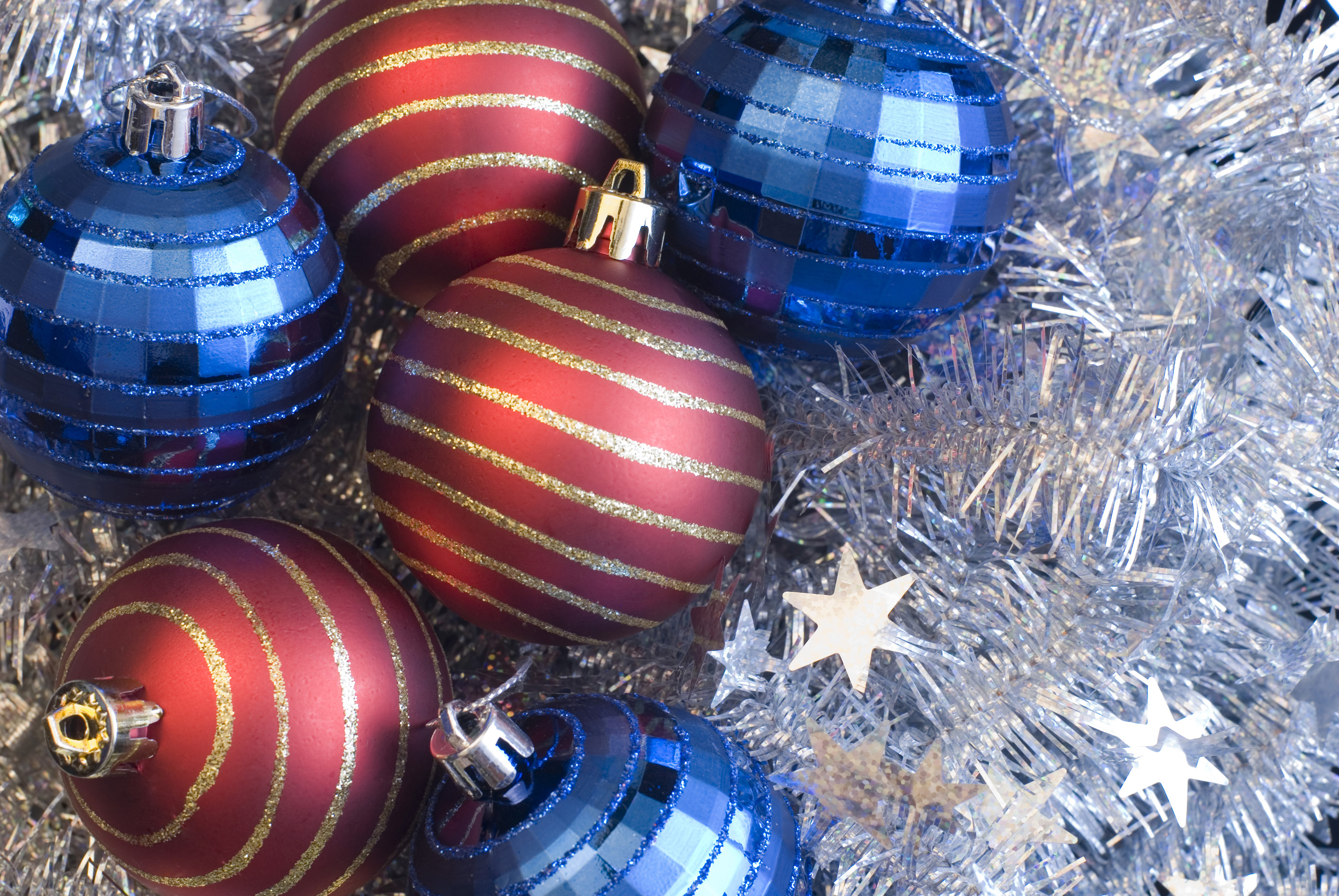 blue and red festive baubles on a background of silver tinsel