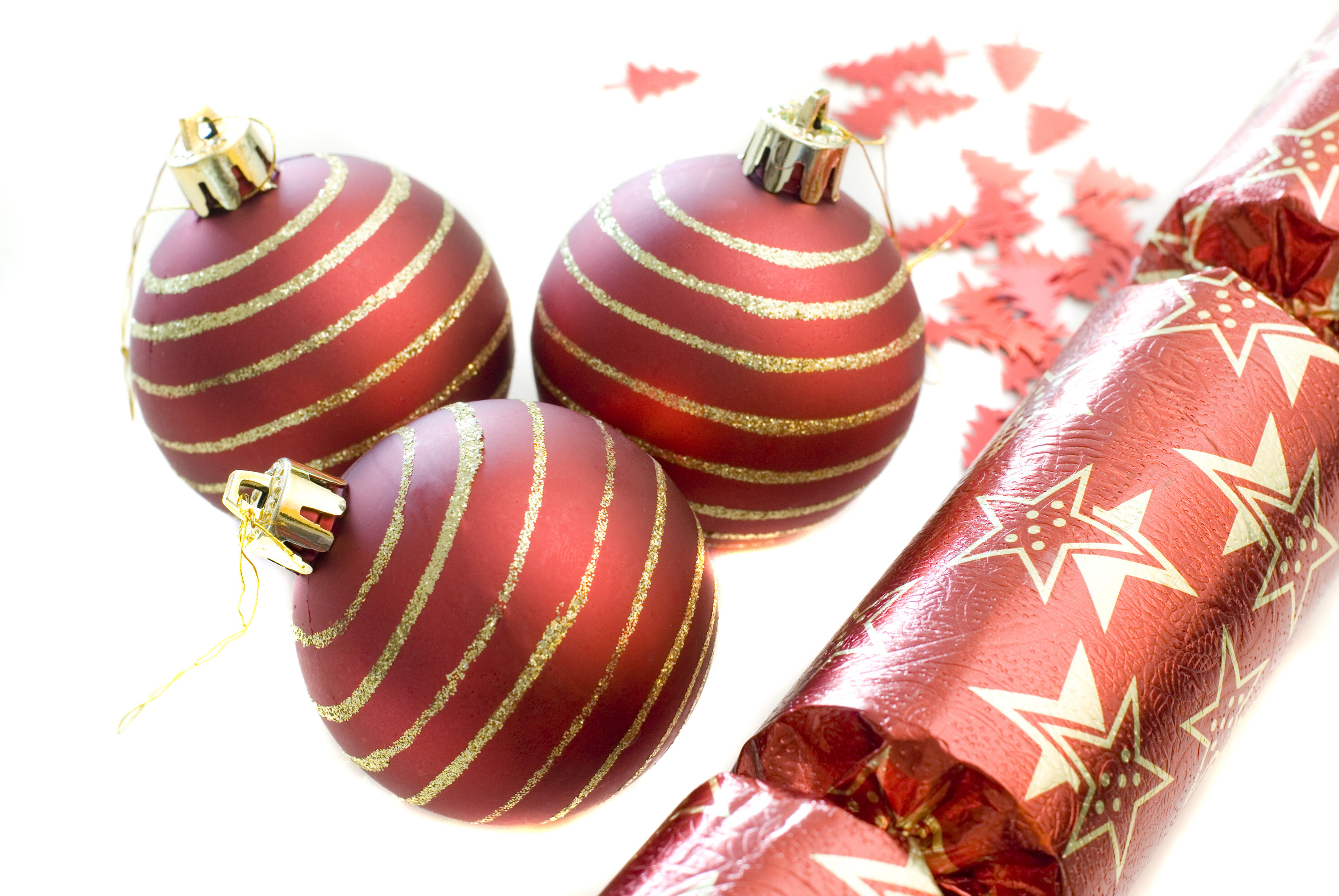 a selection of red coloured christmas baubles cutout on white to form a decorative corner