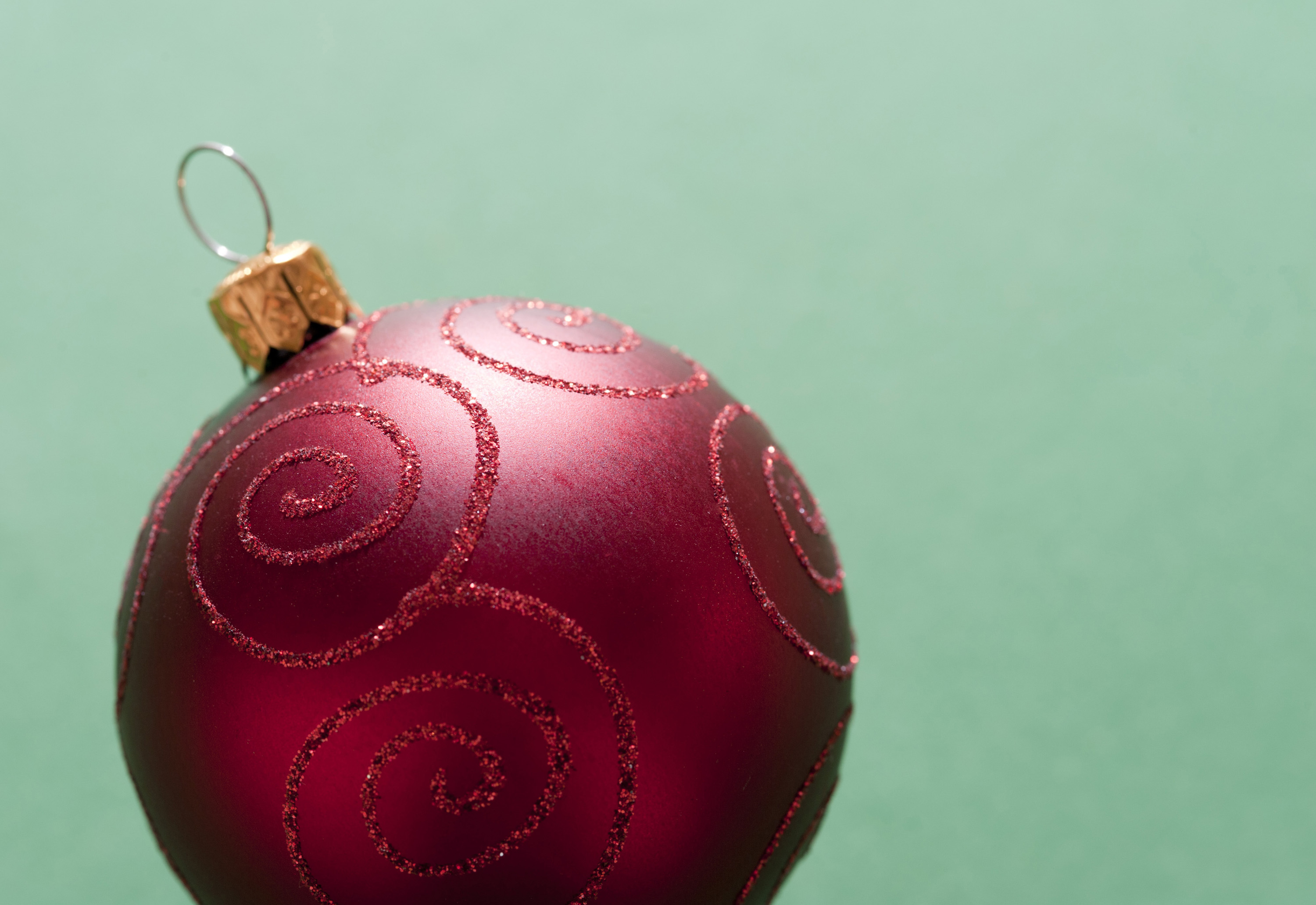 Close-up of red decorative Christmas ball on green background