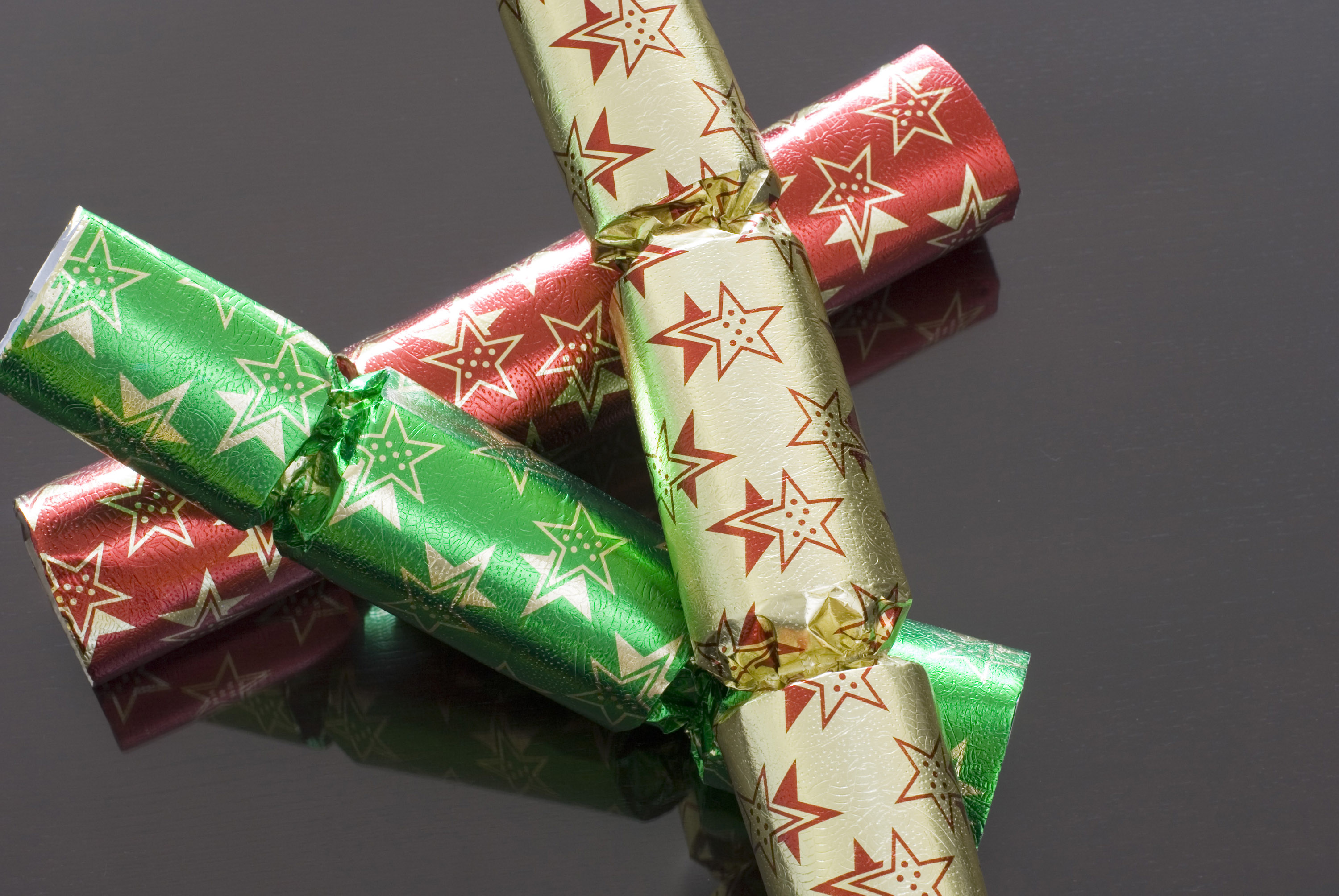 Three different coloured chrismas crackers on a dark polished background