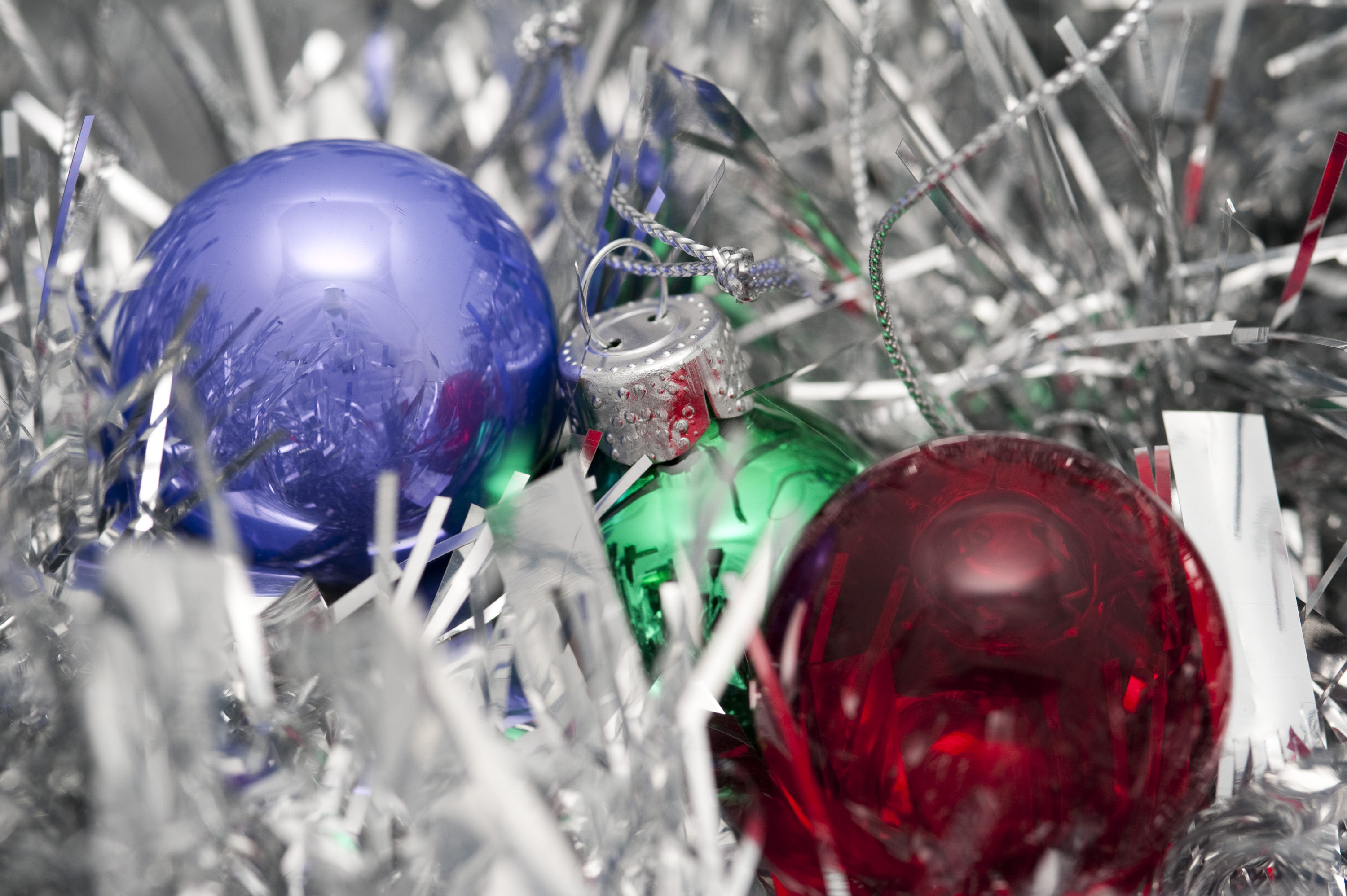 a background image of glass christmas baubles and silver tinsel