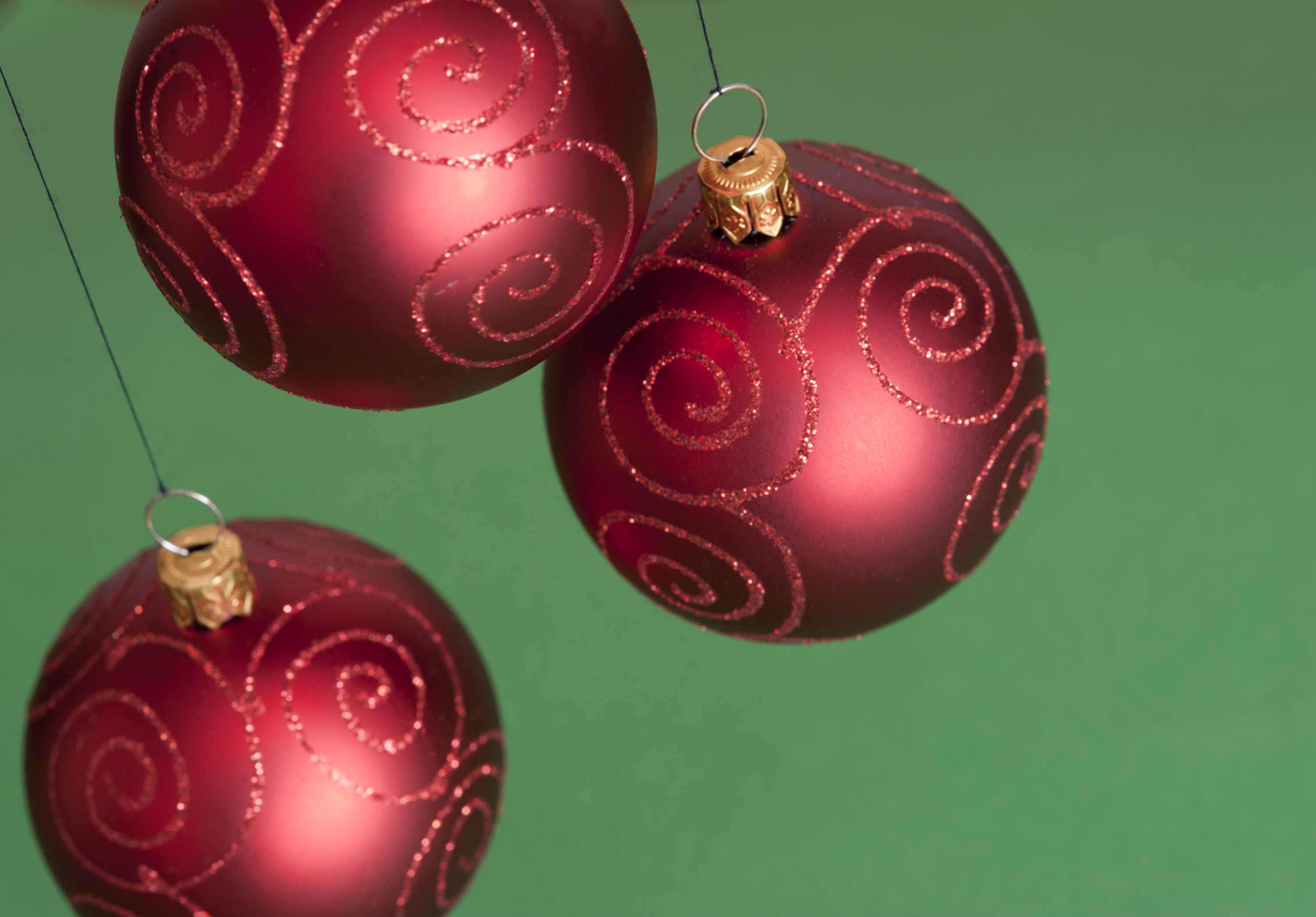 Close-up of three red Christmas balls hanging against of green background