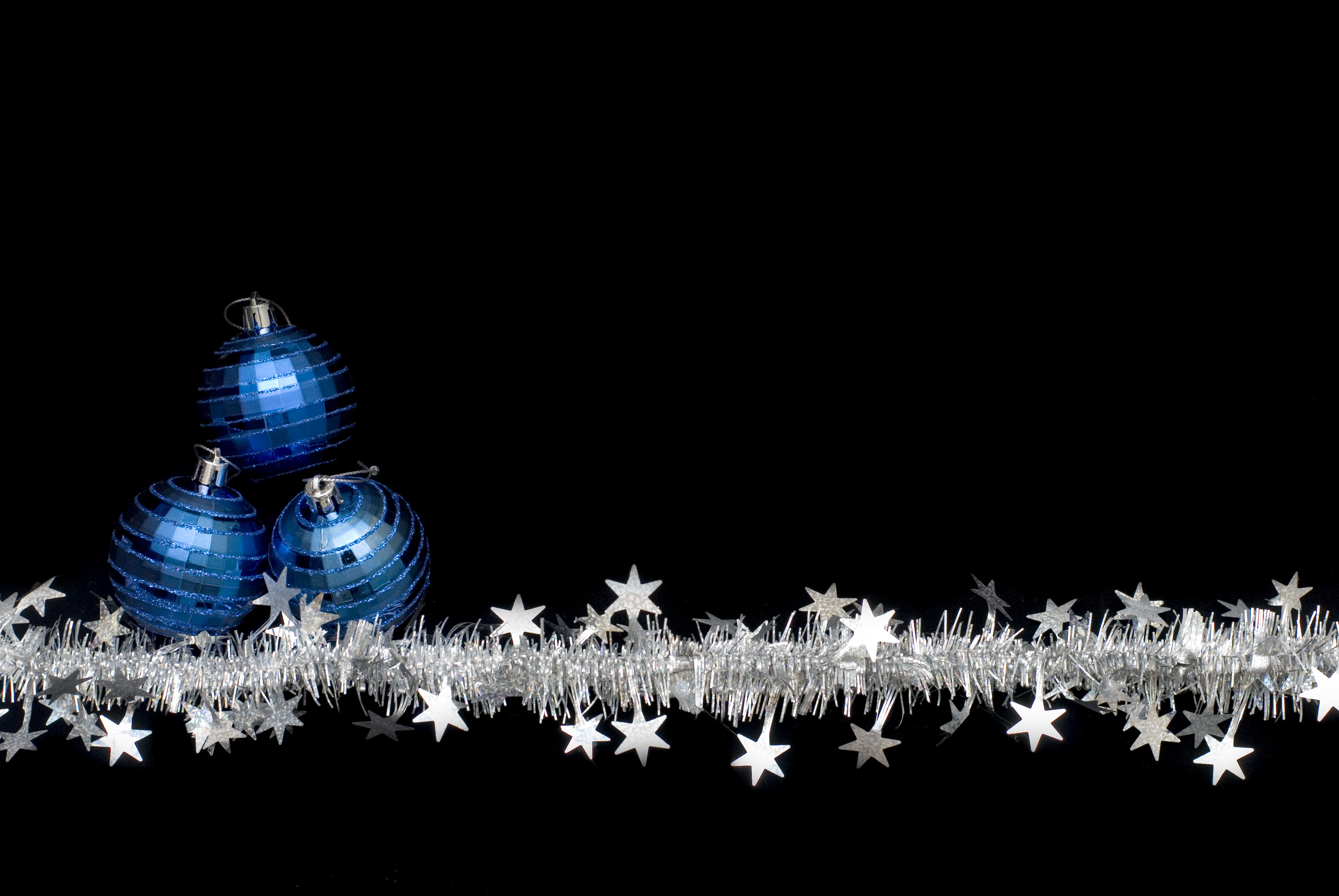 a line of christmas tinsel and blue festive ornaments