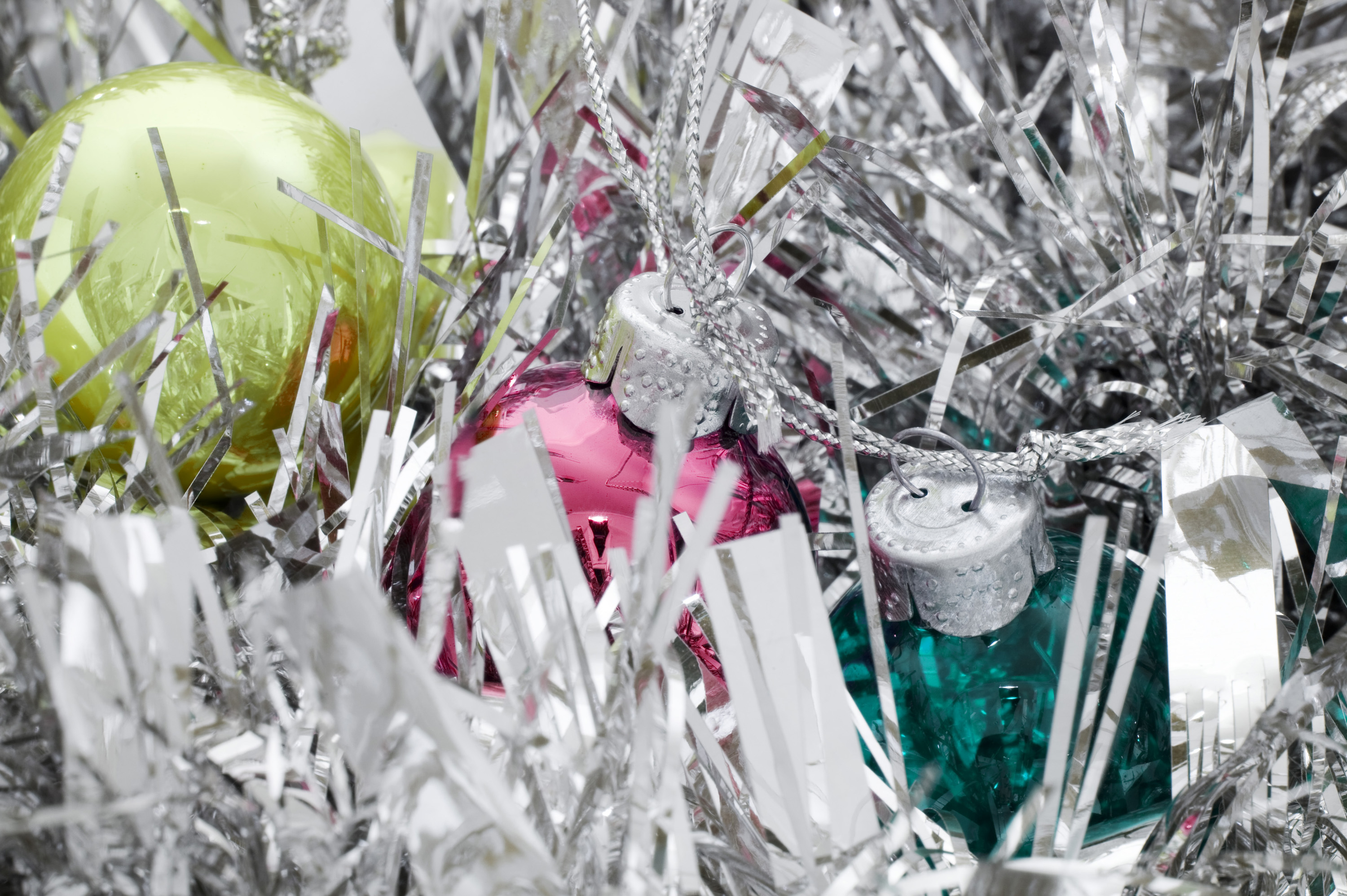 a bright silver background featuring tinsel and christmas ornaments