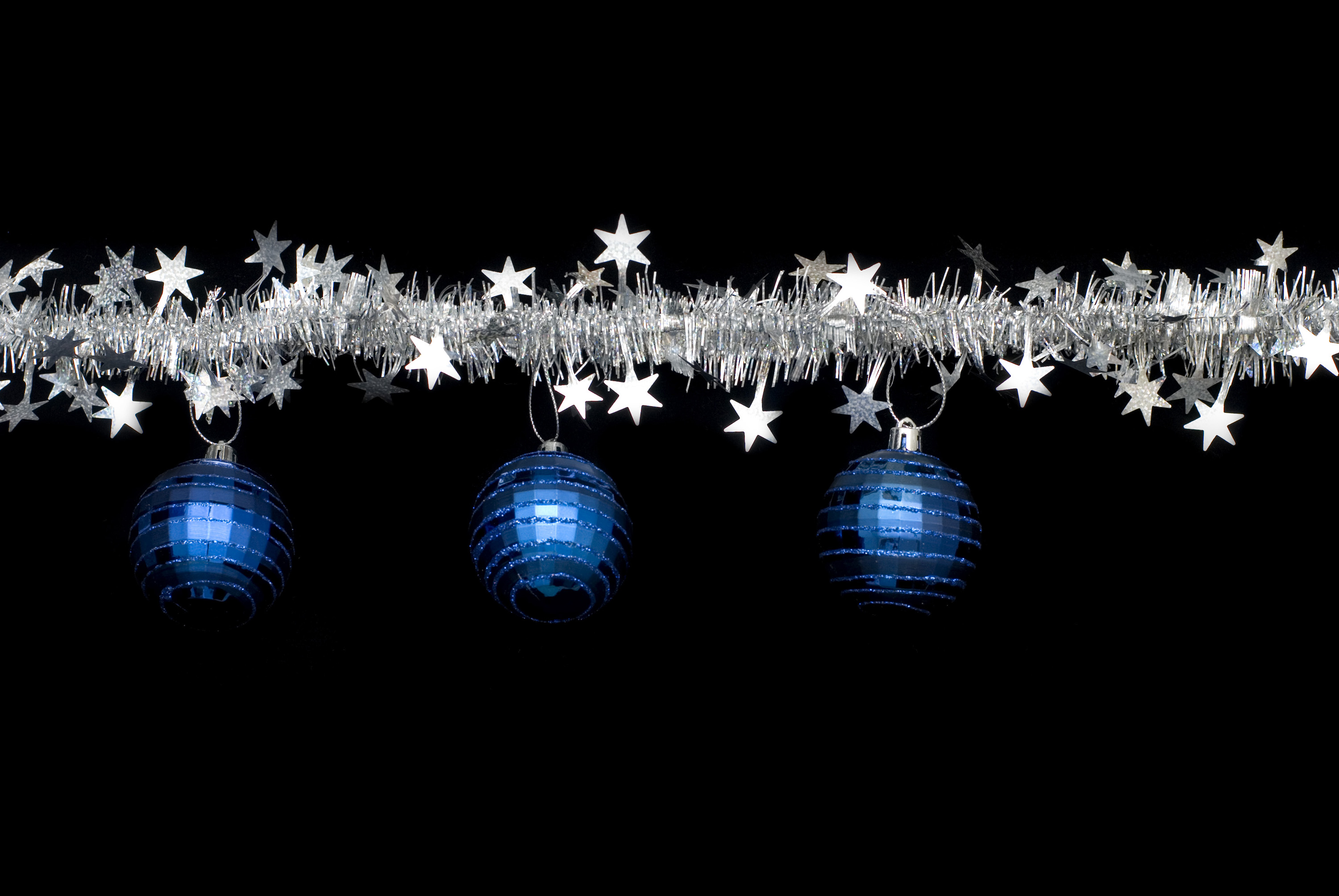 a line of christmas tinsel and blue festive ornaments make a useful border component for a christmas theme design