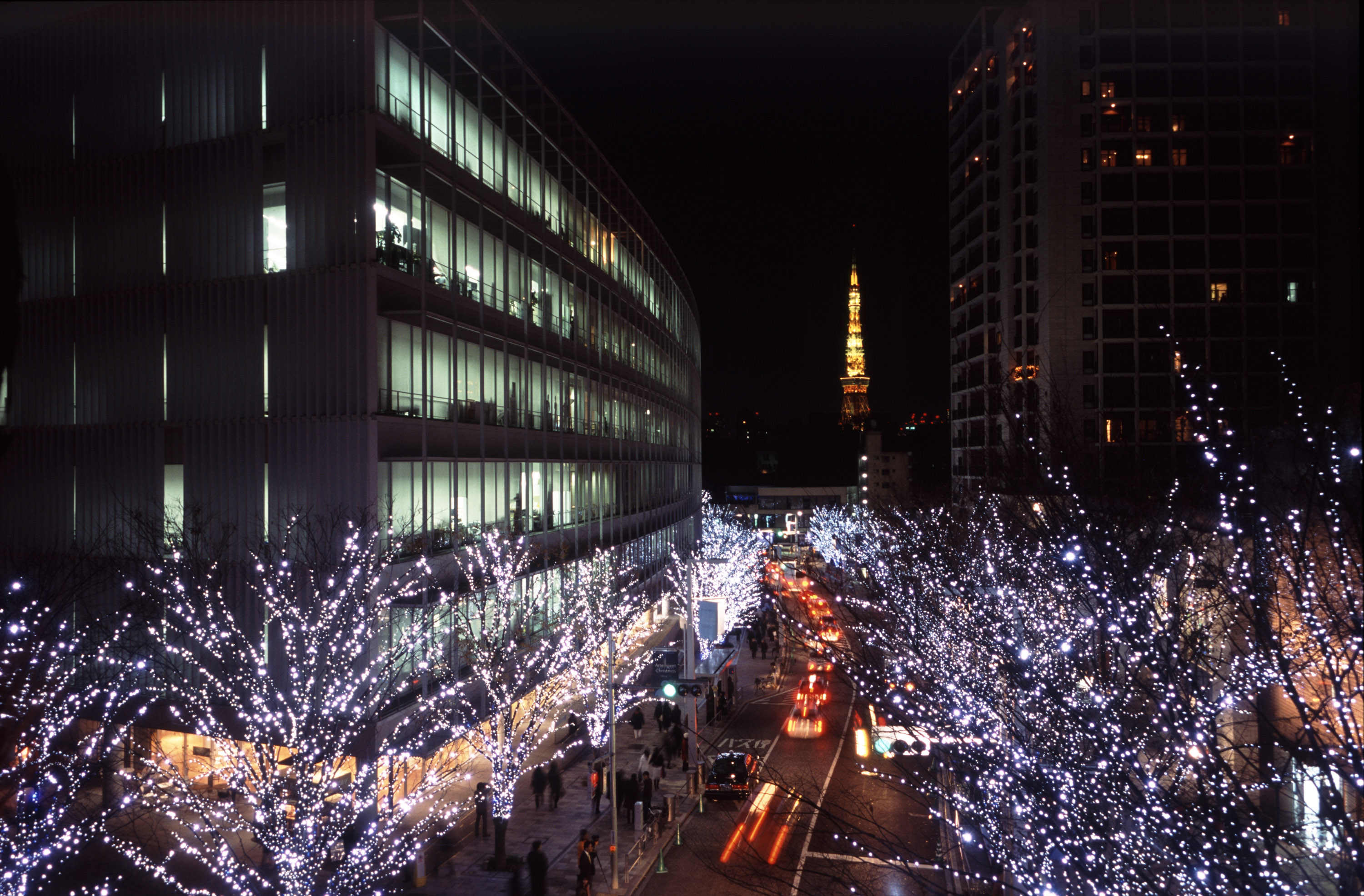 A modern tokyo street scene with christmas lights illuminating a winter evening