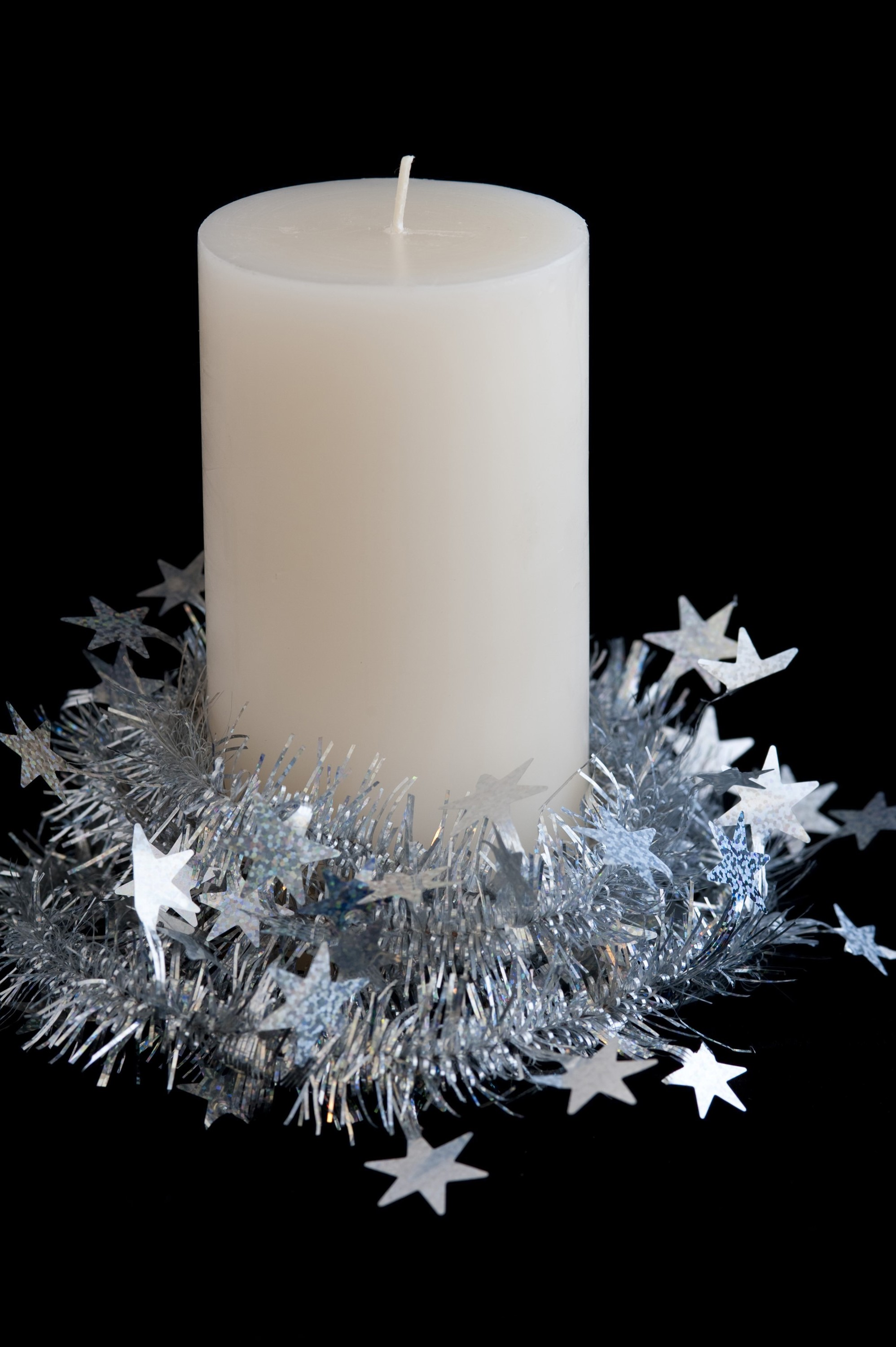a new christmas candle wrapped in tinsel on a black background